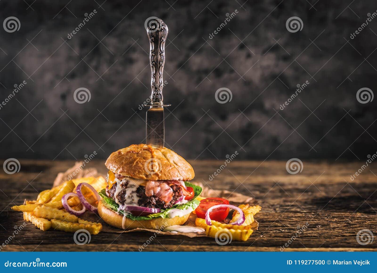 特写镜头家在木ta做了与刀子和油炸物的牛肉汉堡