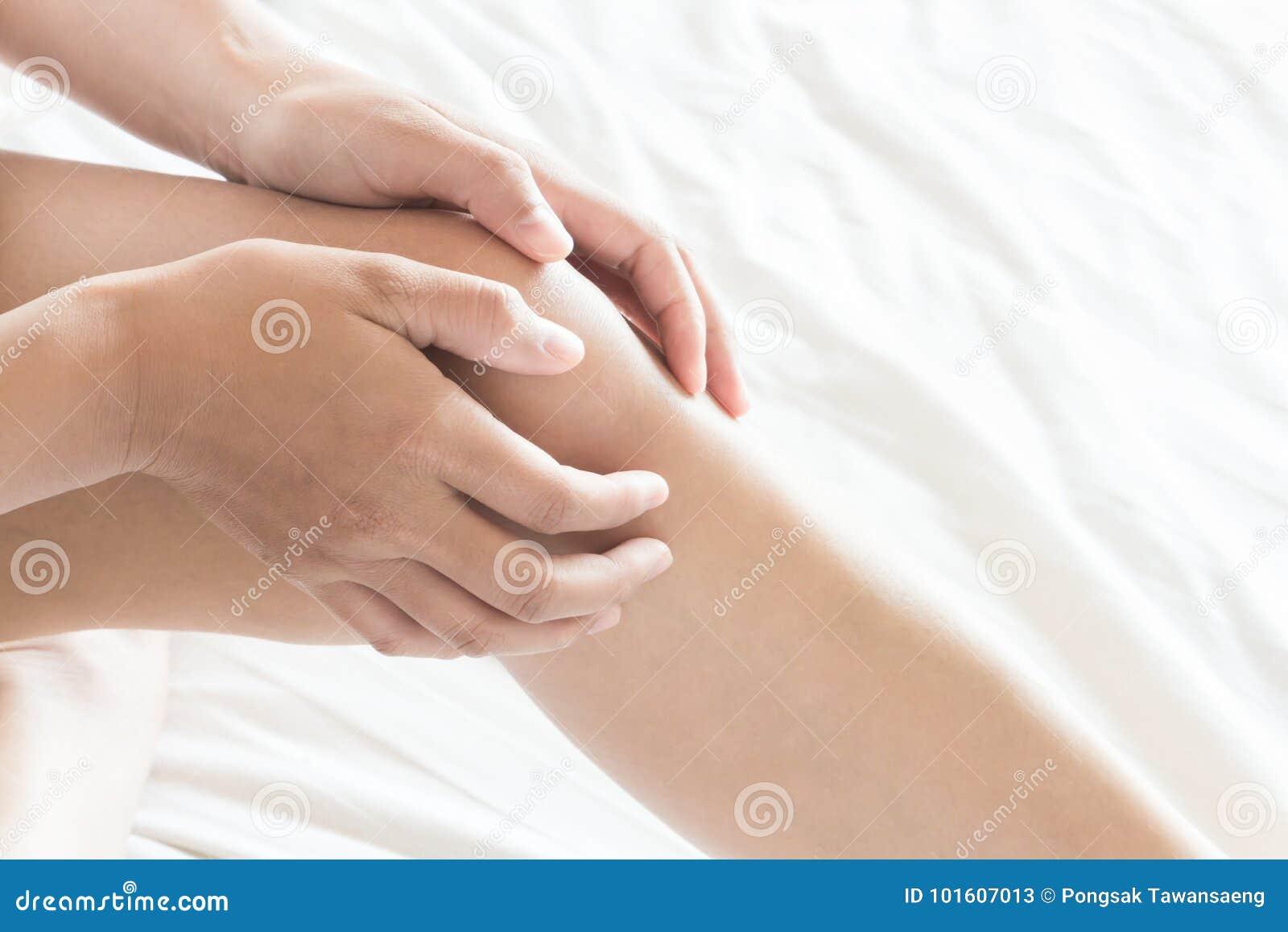 特写镜头拿着充满痛苦在床上,医疗保健的妇女手膝盖
