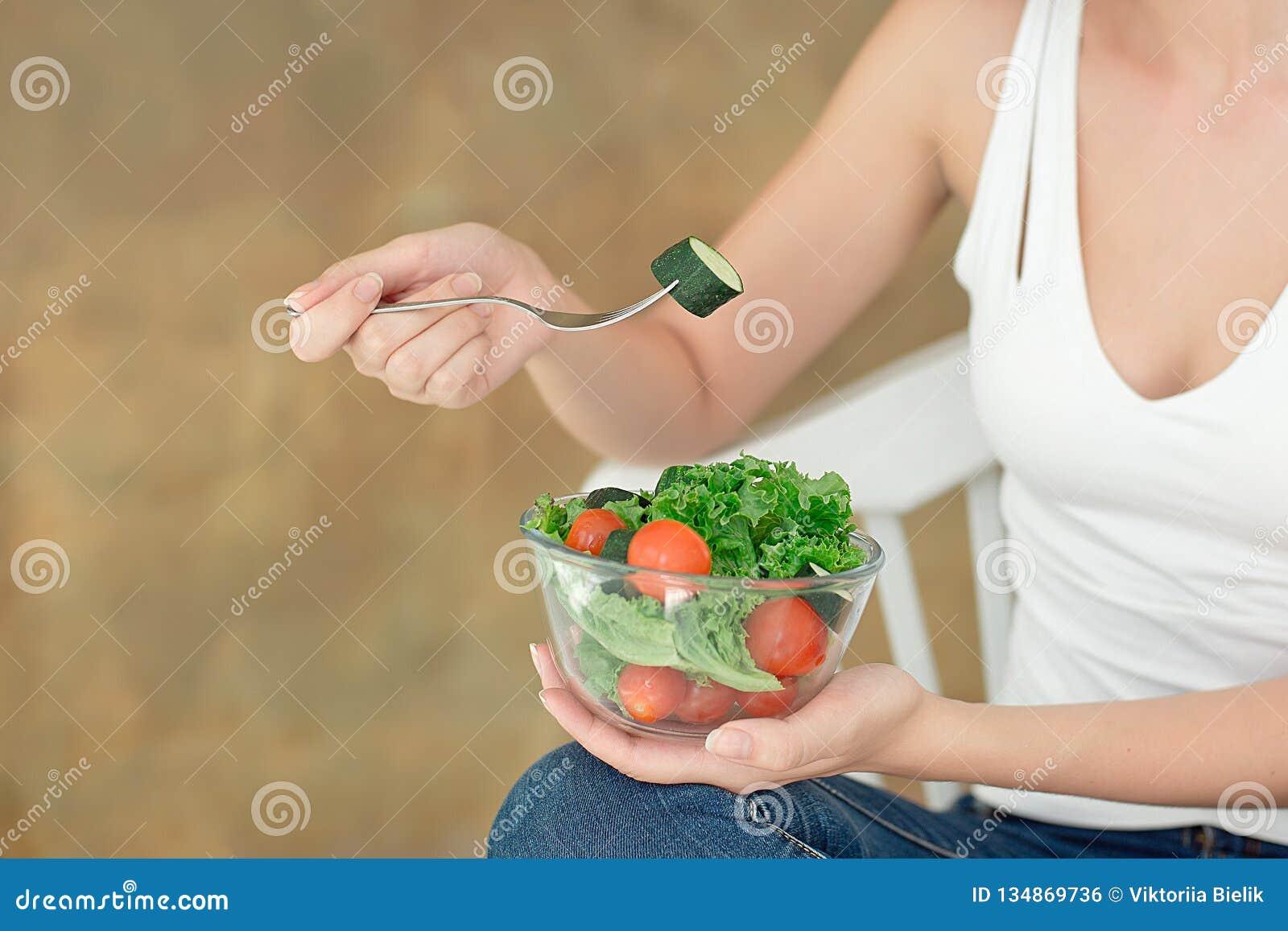 特写镜头拿着碗新鲜蔬菜沙拉的背面图妇女拿着叉子手中