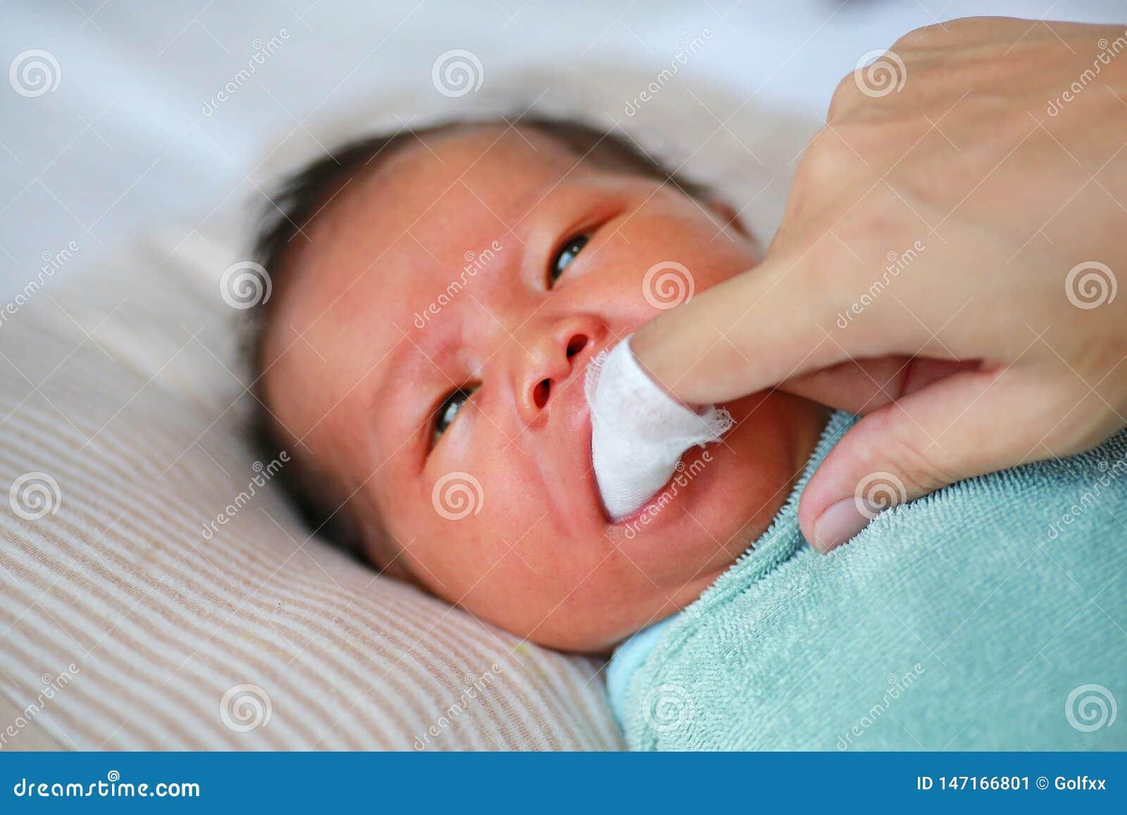 特写镜头母亲手干净的婴孩舌头和胶与干净的纱