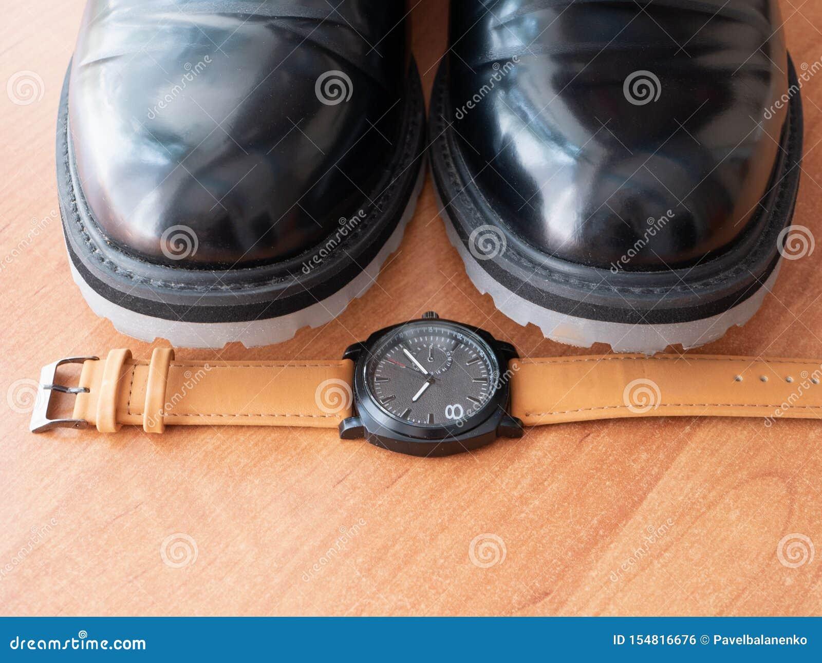 特写镜头由对时髦的典雅的黑经典鞋子人手表