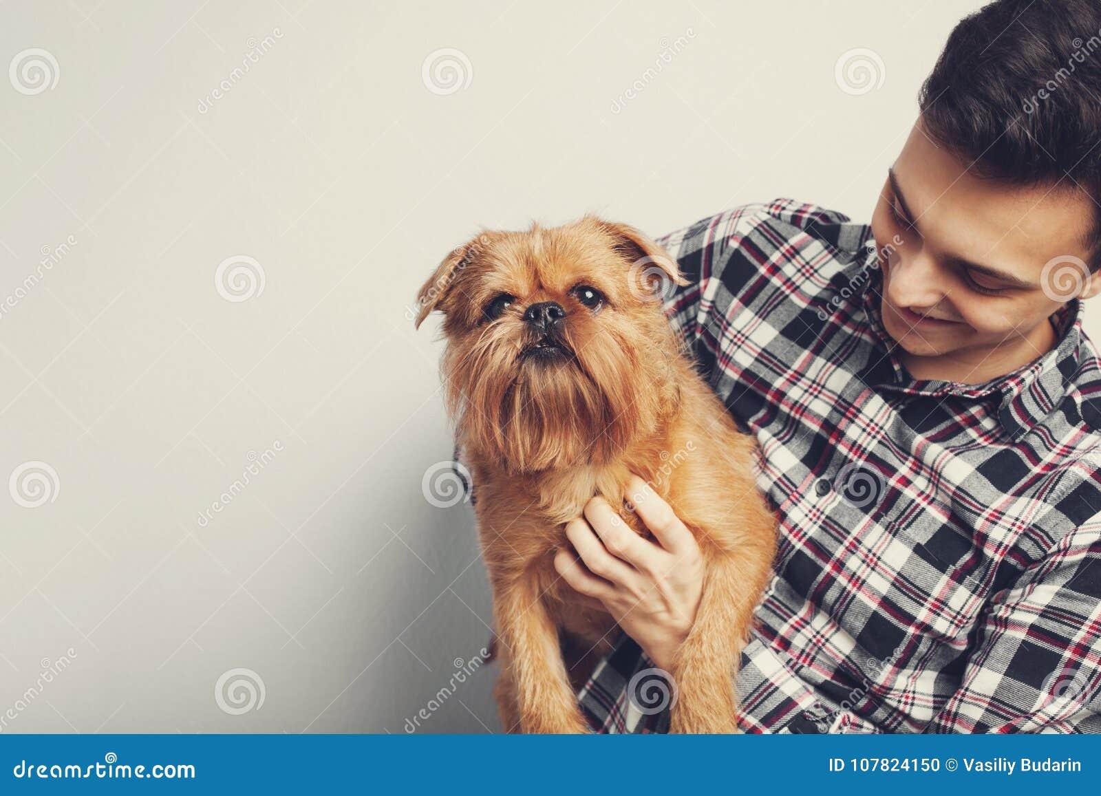 特写镜头画象英俊的年轻行家人,亲吻他的好朋友红色狗隔绝了轻的背景 正面人的情感, f