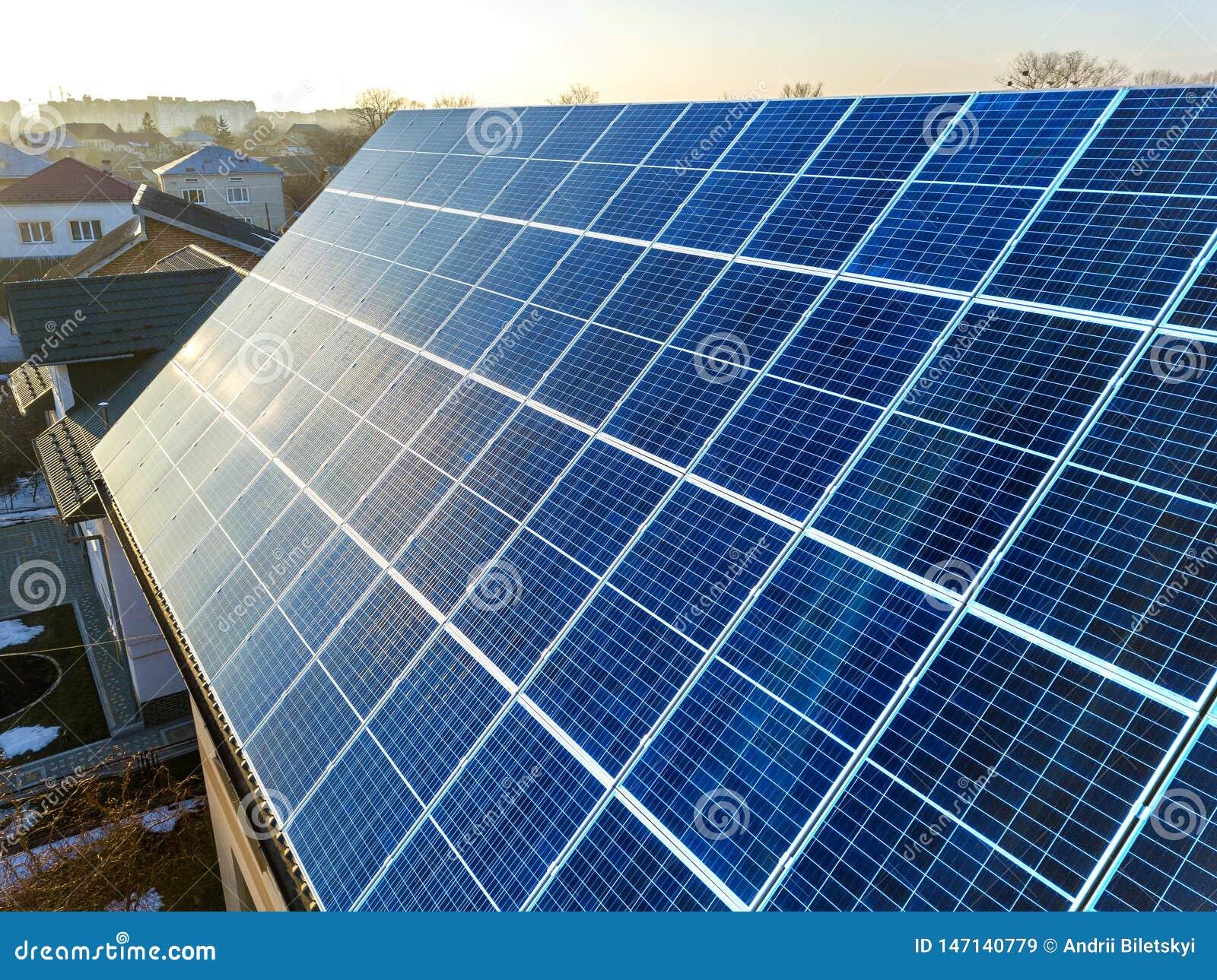 特写镜头表面点燃由在大厦屋顶的太阳蓝色发光的太阳照片流电盘区系统 可更新的生态绿色能量