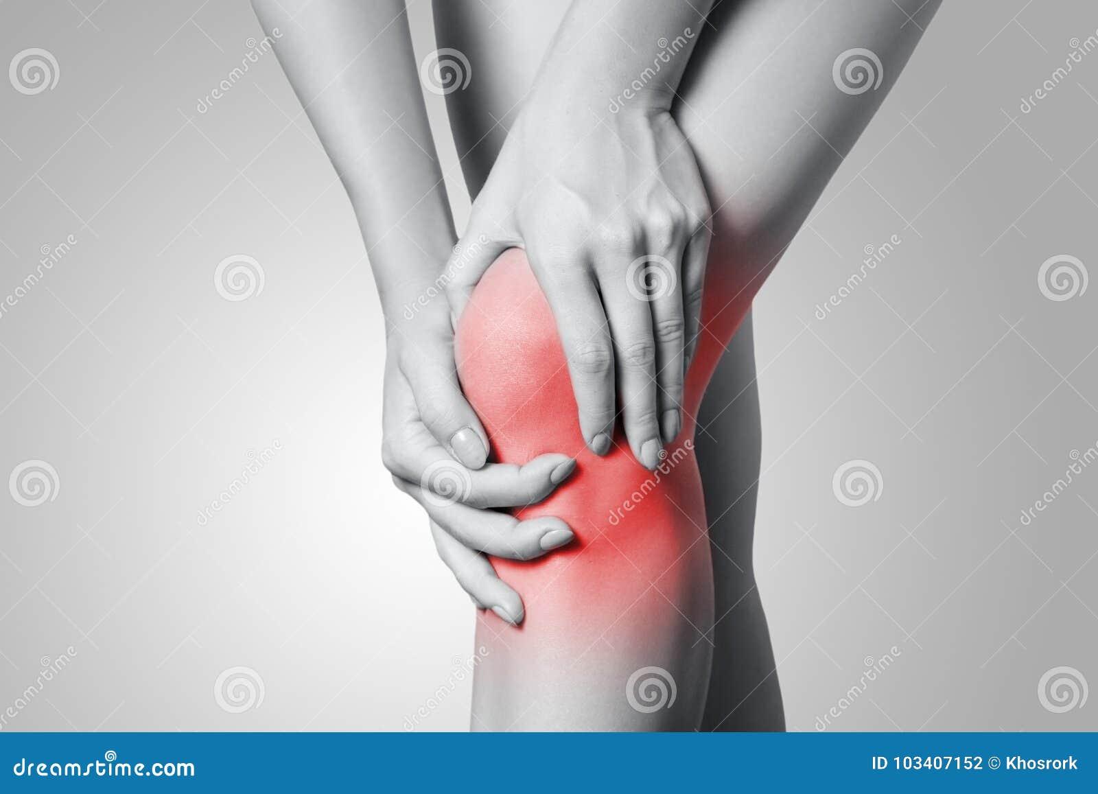 特写镜头观点的充满膝盖痛苦的一个少妇在灰色背景