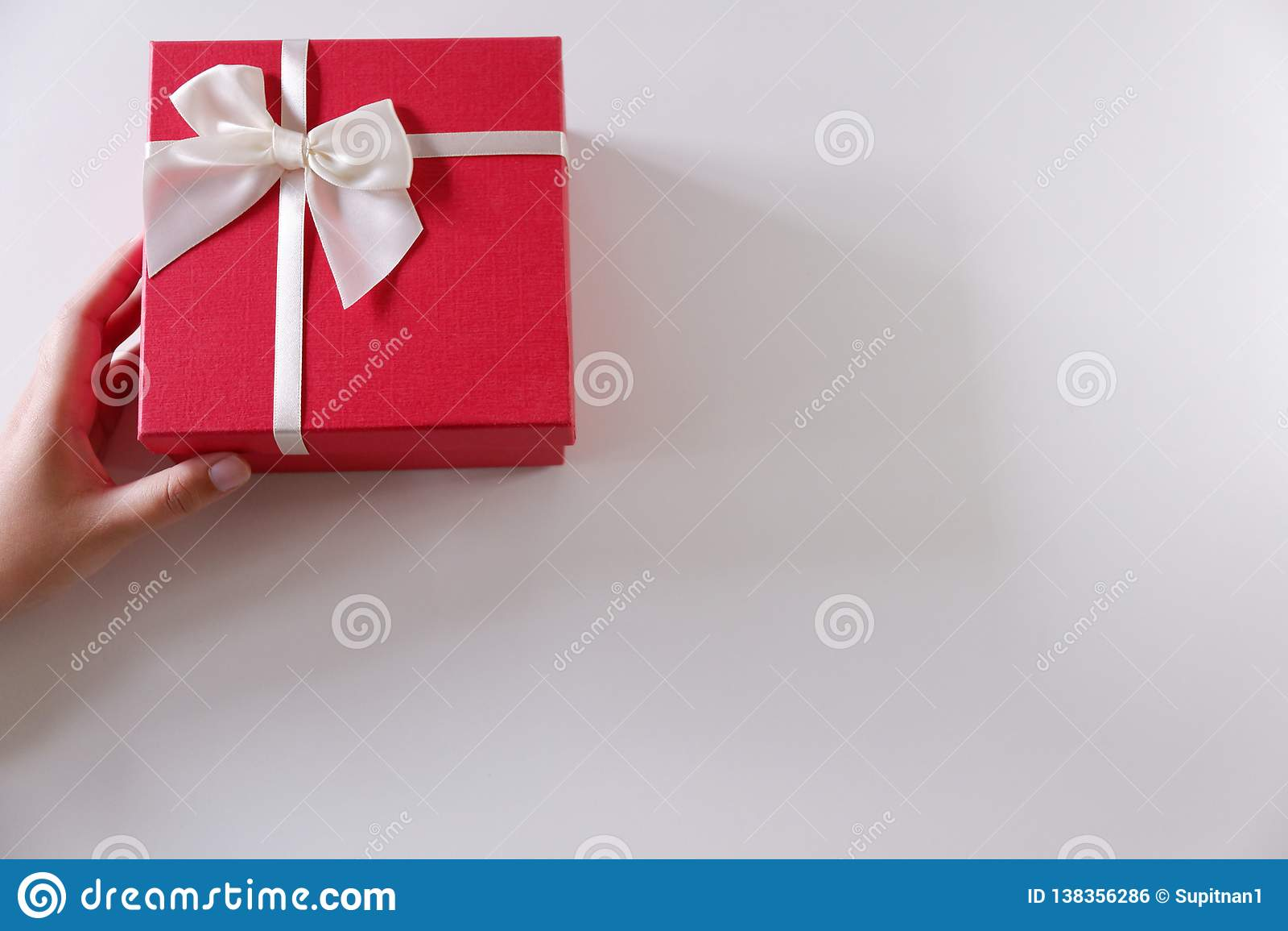 特写镜头送有白色丝带的妇女手红色礼物盒在白色背景