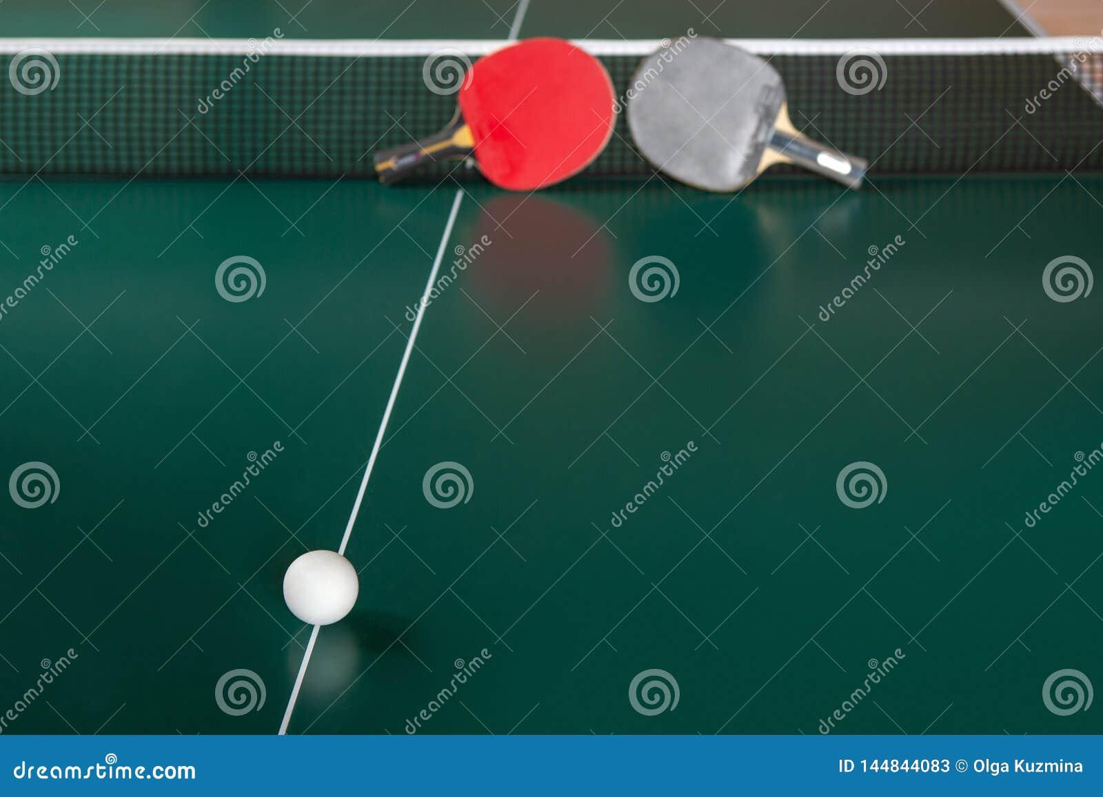 两副乒乓球球拍和一个球在一个选材台上