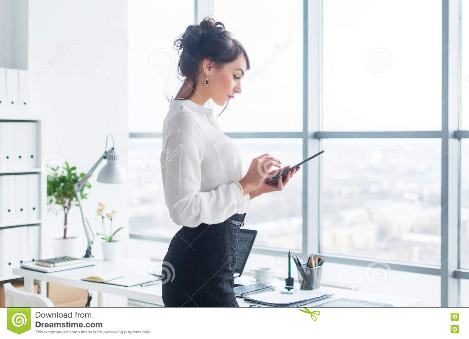 特写镜头发短信给,传送和读信息的雇员的侧视图画象在她的断裂期间在工作场所