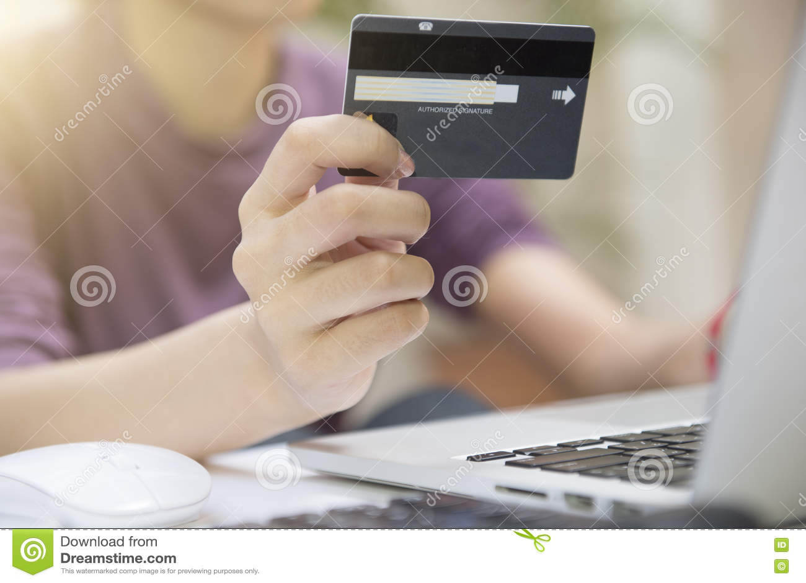 特写镜头拿着信用卡和使用计算机的妇女的手