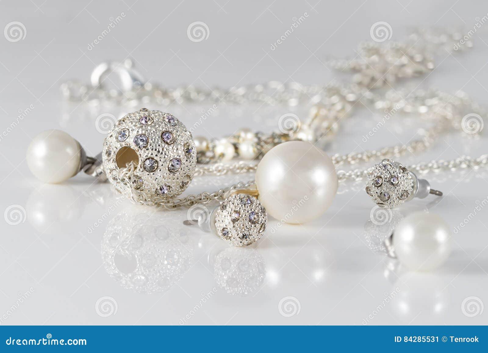 特写镜头首饰套散布的银色耳环和垂饰丙烯酸酯的表面上在灰色背景