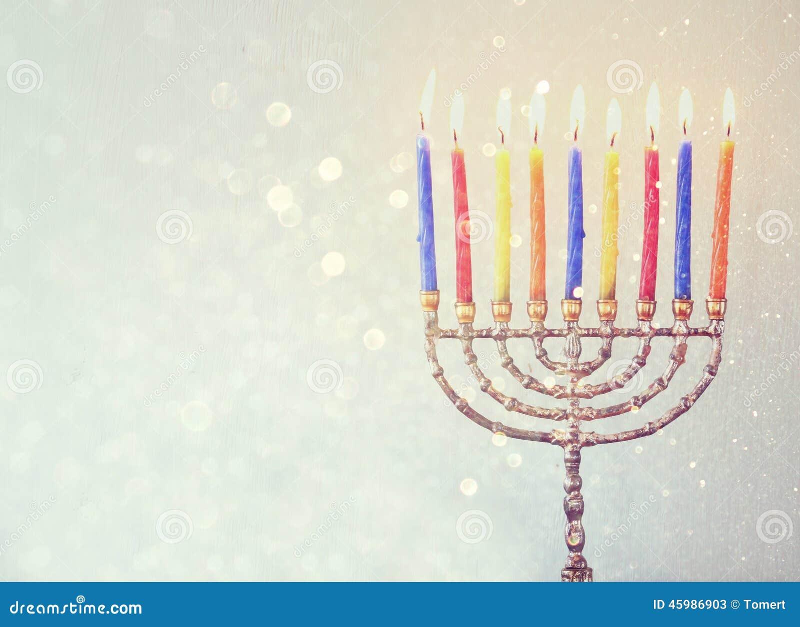 犹太假日光明节背景的低调图象与menorah灼烧的蜡烛的在闪烁背景
