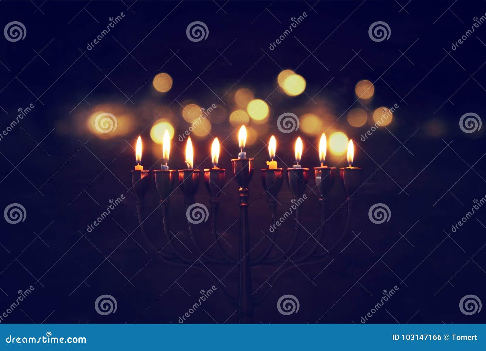 犹太假日光明节背景的低调图象与menorah & x28的; 传统candelabra& x29;并且燃烧的蜡烛