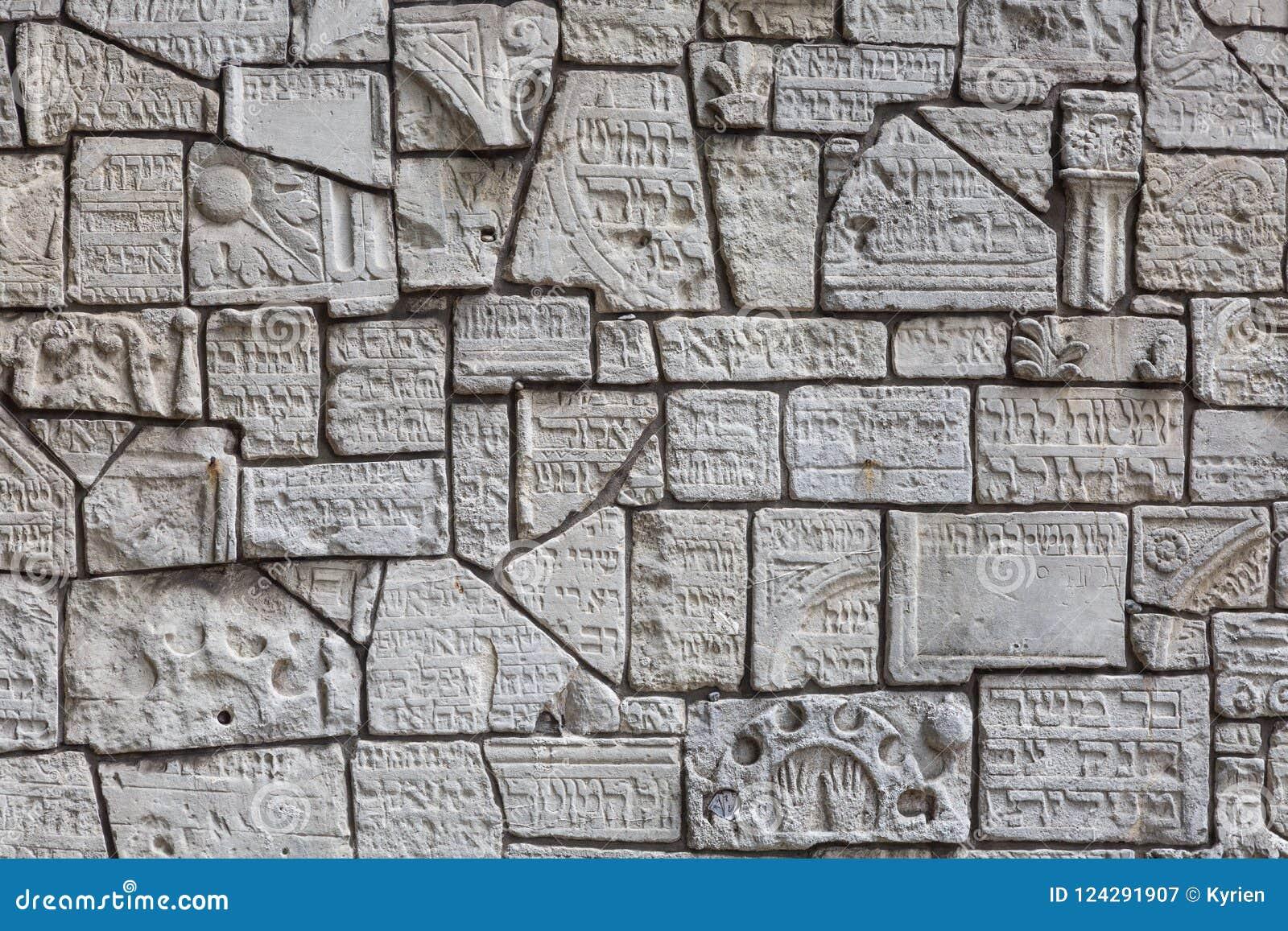 犹太墓碑的片段在墙壁上的在犹太公墓