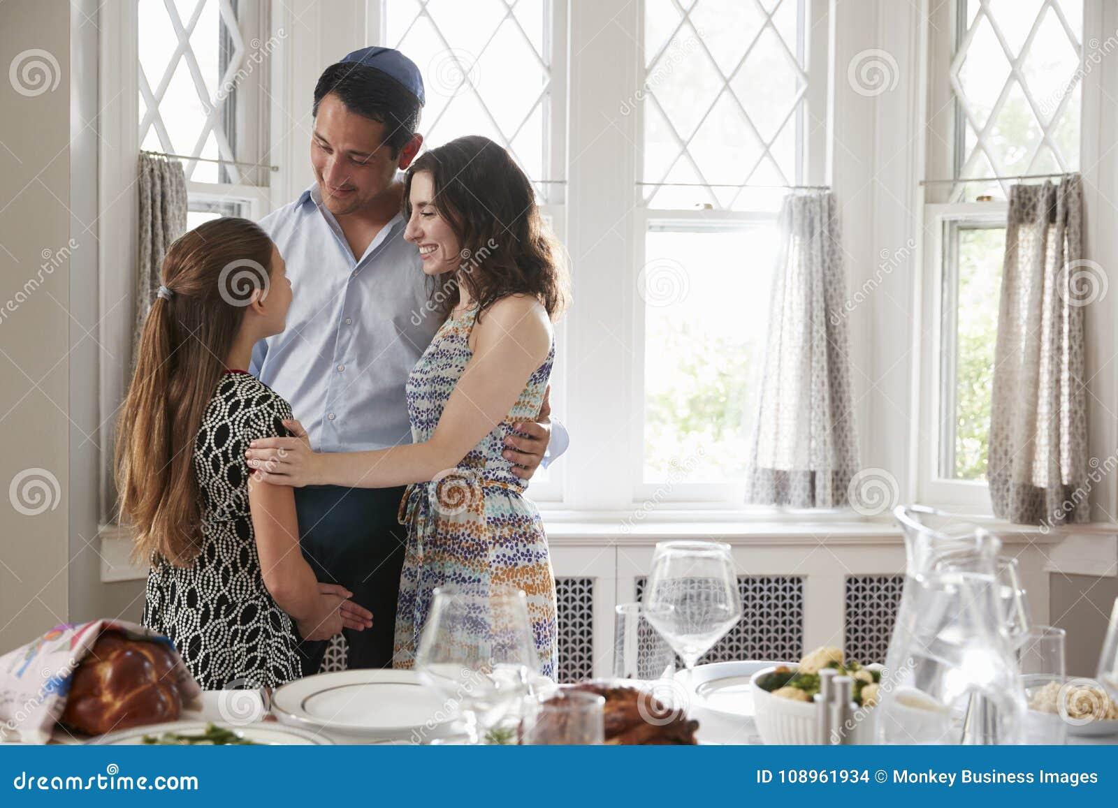 犹太拥抱在Shabbat膳食前的夫妇和女儿
