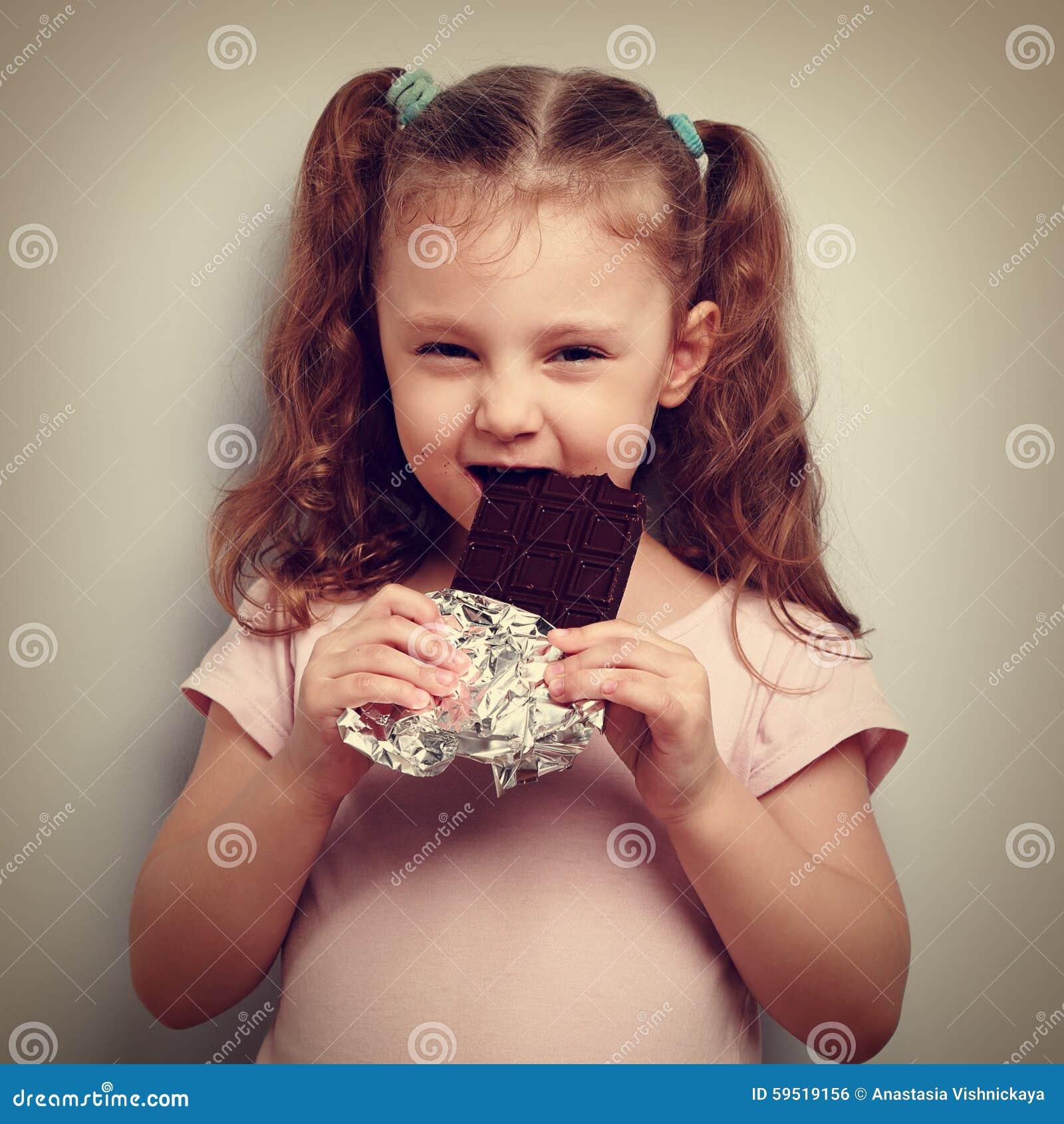 狡猾孩子女孩吃黑暗的巧克力高兴地的和好奇