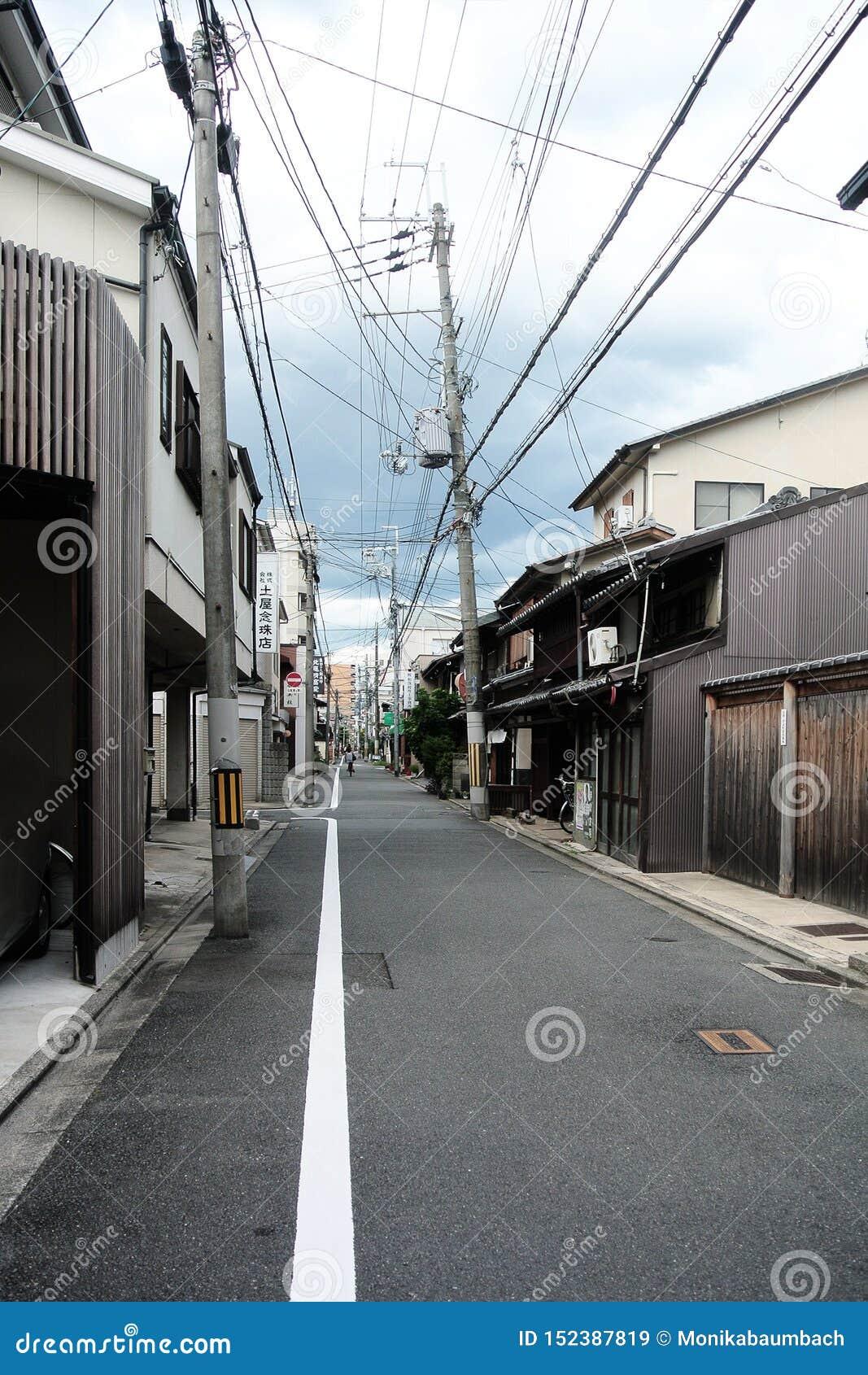 狭窄的农村街道在京都有老传统日本大厦的由木头和弯曲的电源杆做成