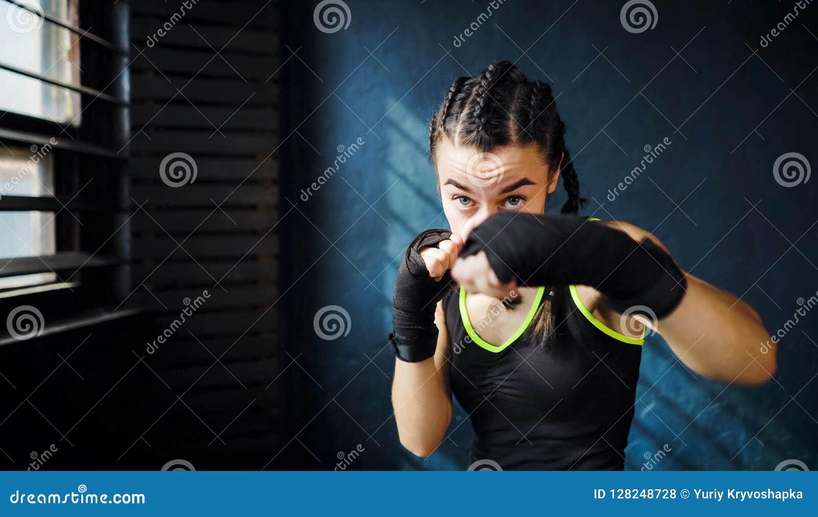 猛击在健身房自由空间, copyspace的画象美好的年轻拳击妇女训练