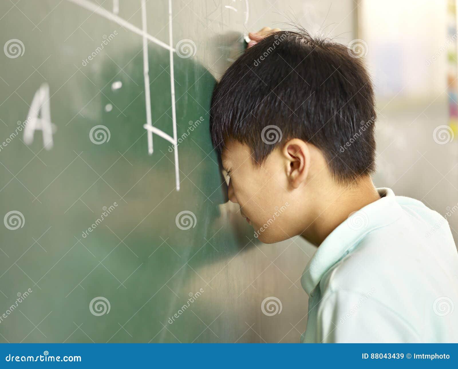 猛击他的在黑板的痛苦的亚洲学生头