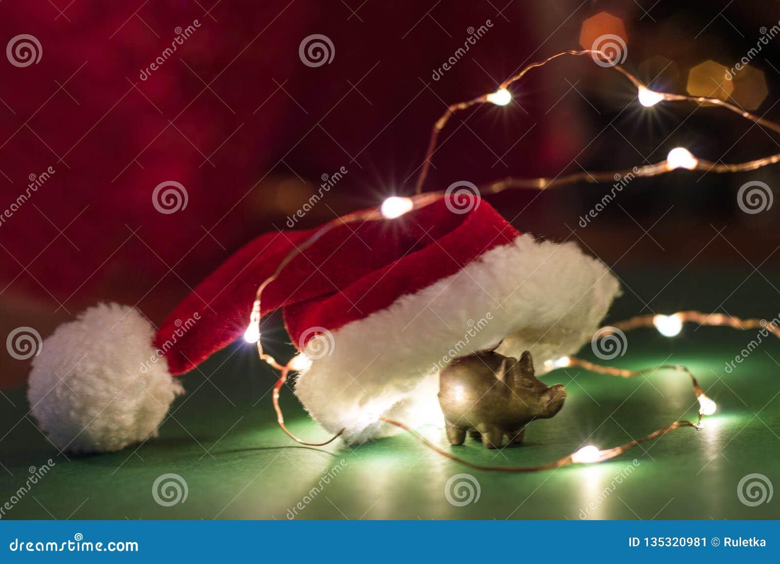 猪,新年的概念金黄小雕象与圣诞老人帽子的
