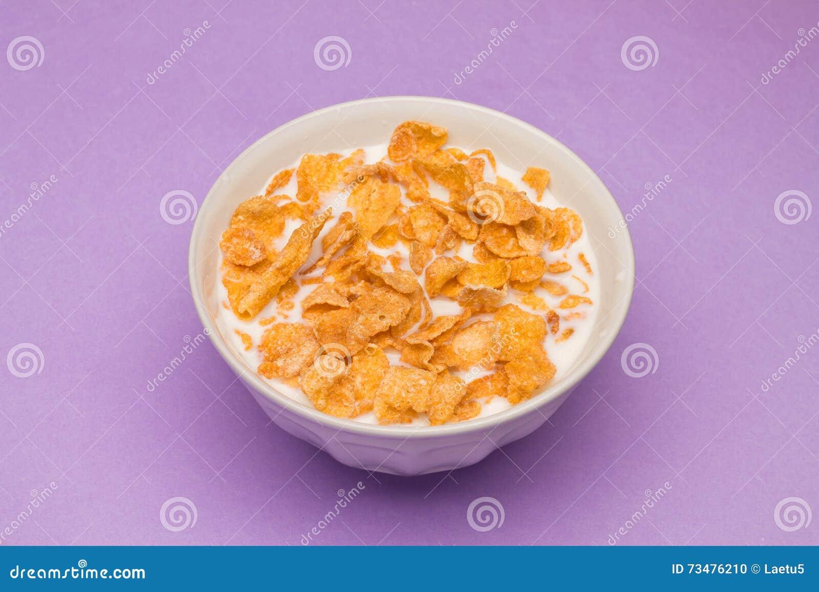 玉米片用在桃红色背景的牛奶
