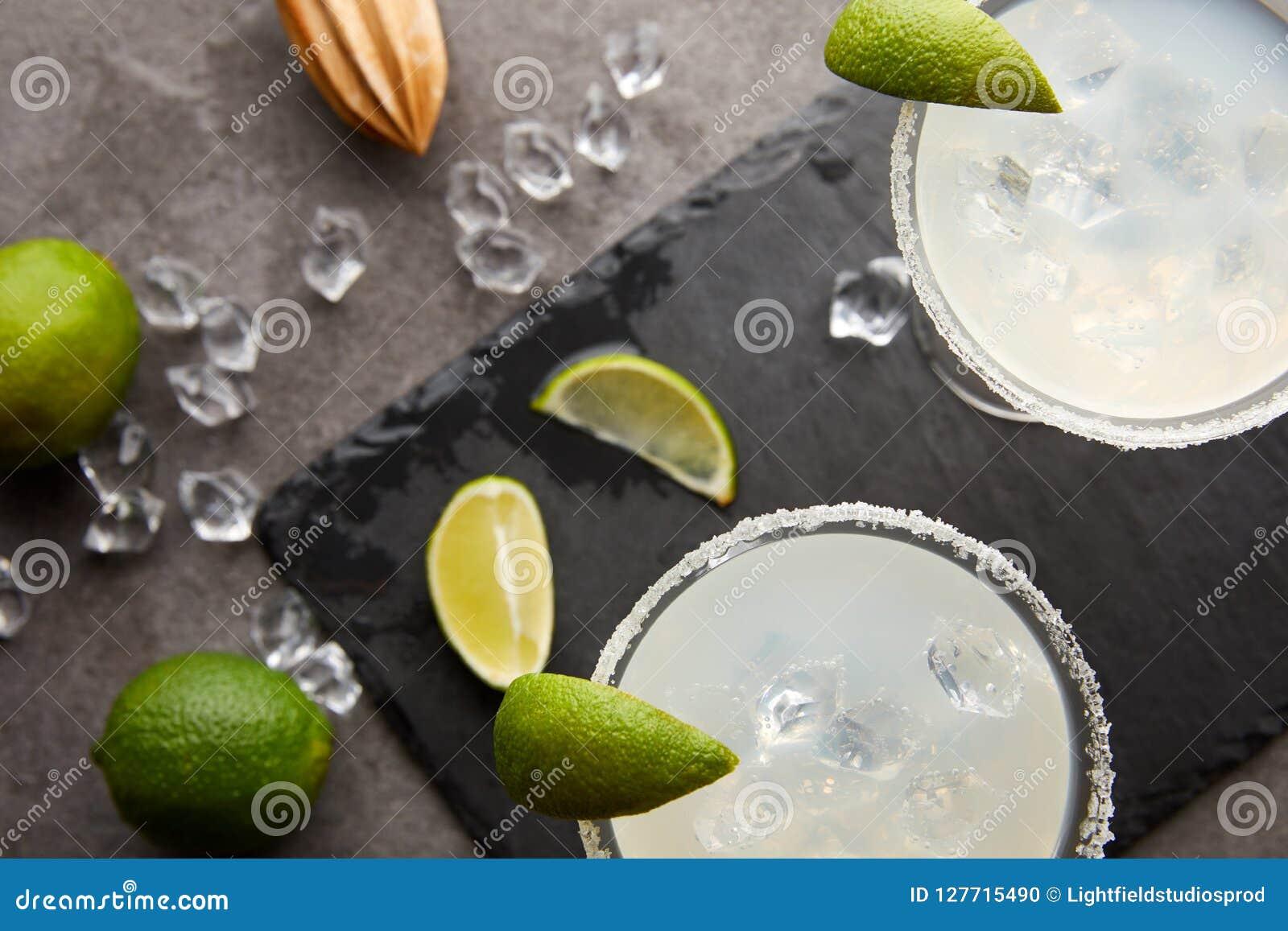 玛格丽塔酒鸡尾酒顶视图与石灰、冰块和木剥削者片断的在灰色桌面