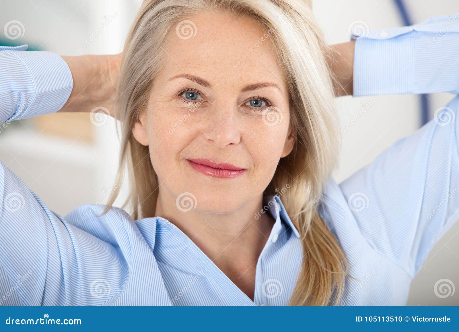 现代女实业家 美好的中部变老了看与微笑的妇女照相机,当选址在办公室时