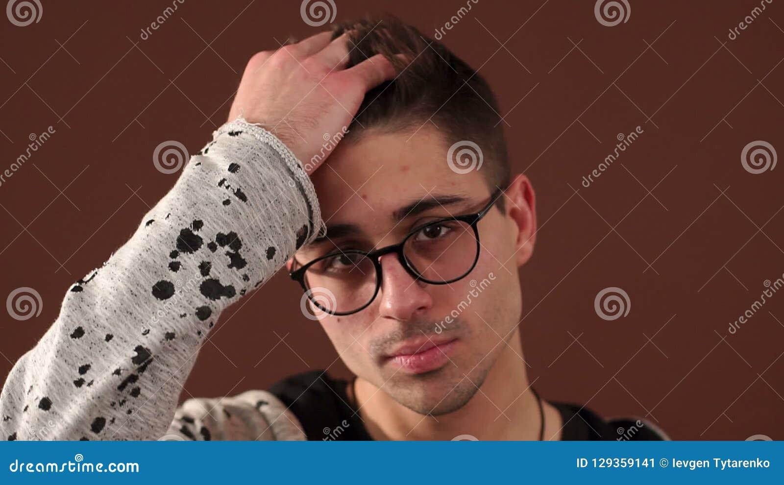 现代年轻人画象戴眼镜的,他通过他的头发运载他的手 股票录像