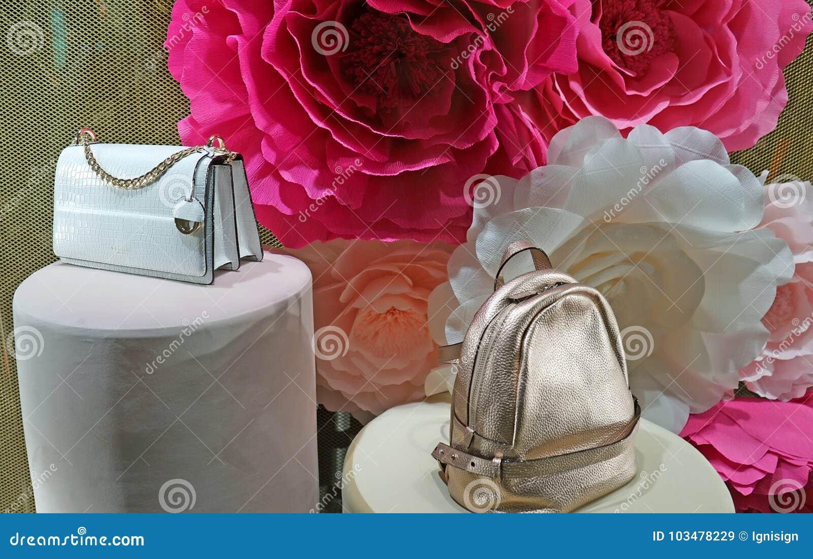 现代提包在玫瑰背景的一个商店窗口里  Oroton是澳大利亚人豪华时装配件公司