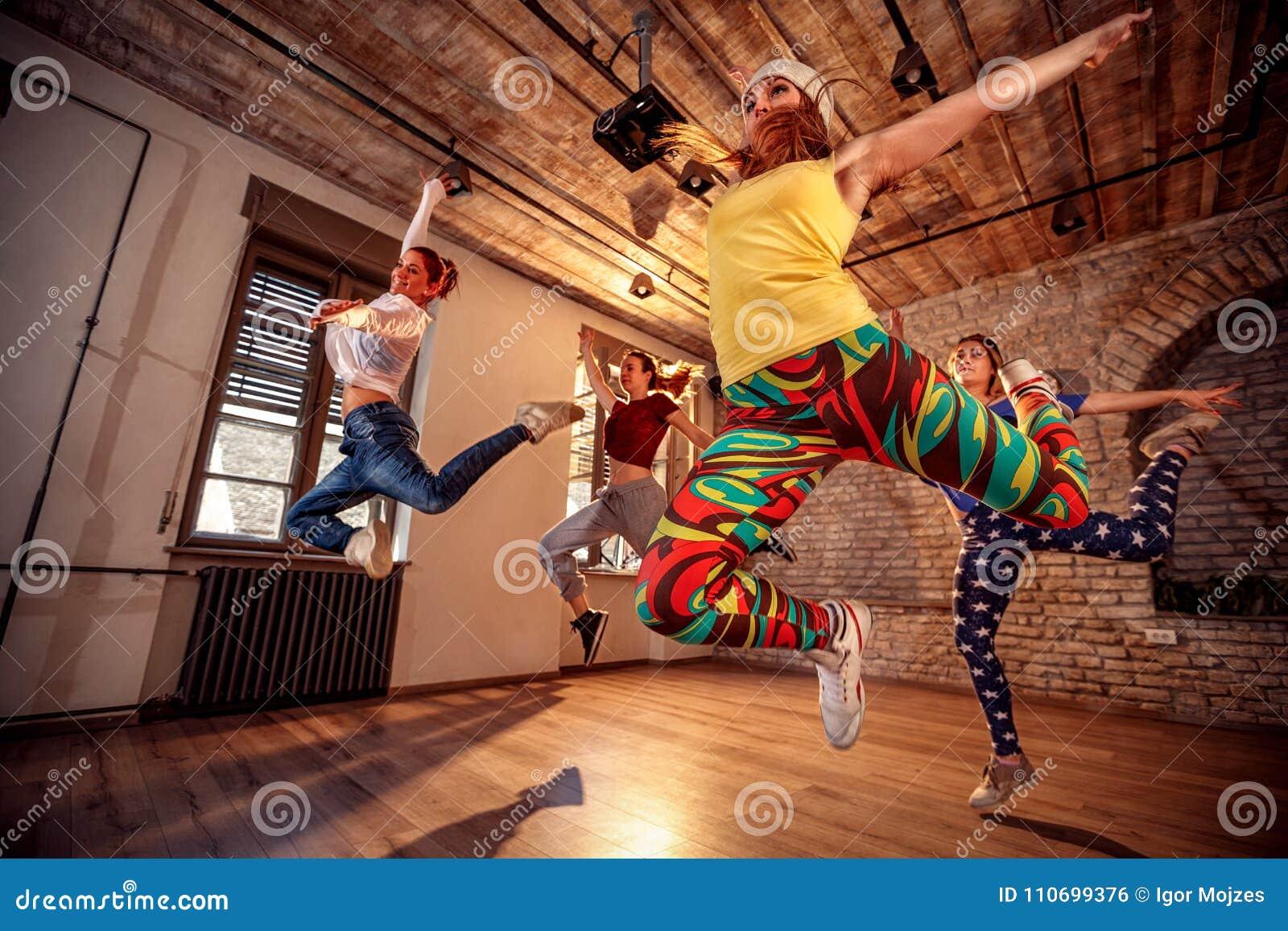 现代舞蹈家跳跃在音乐期间的小组