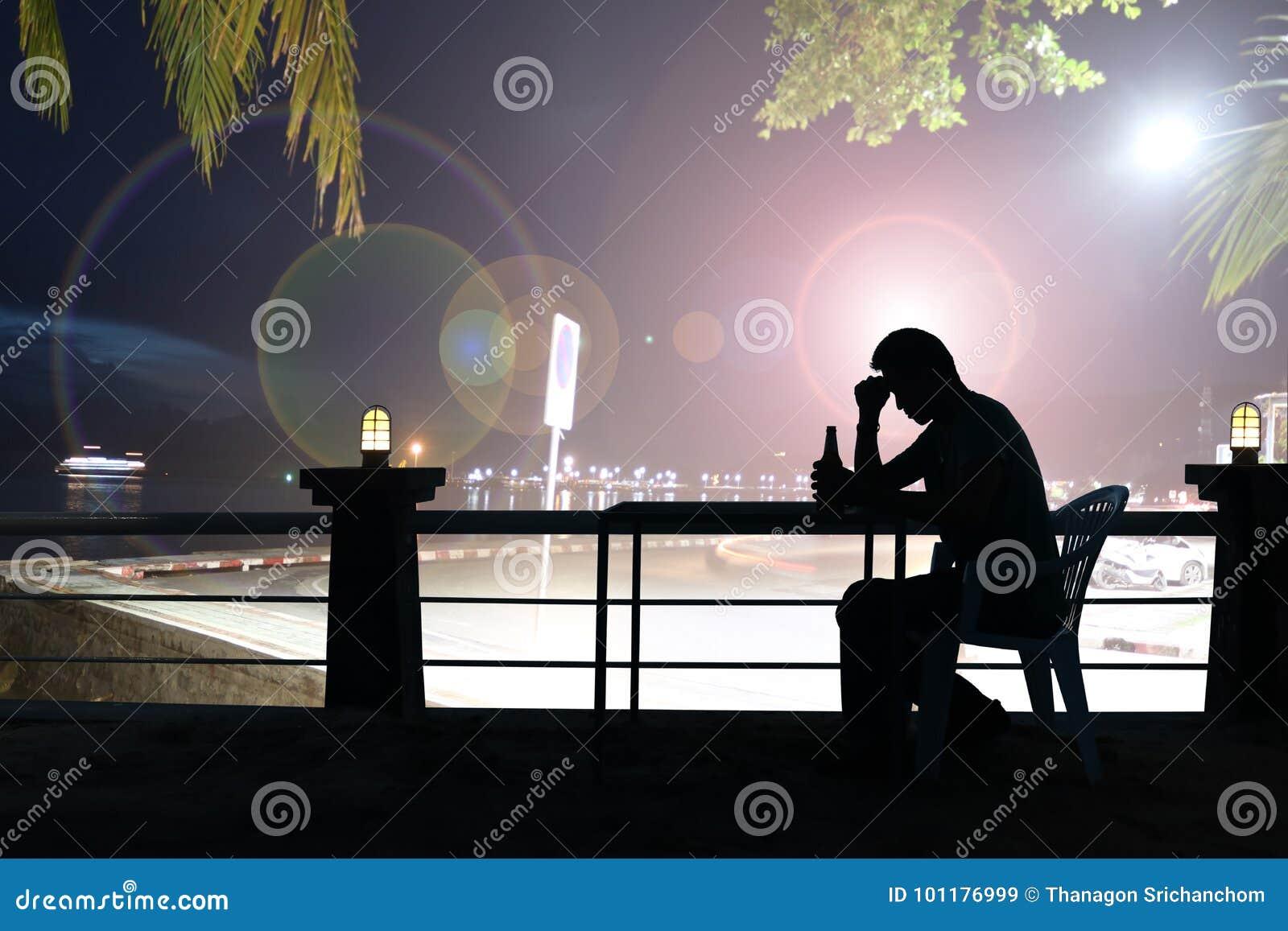 现出轮廓哀伤的人饮用的啤酒在酒吧,夜光