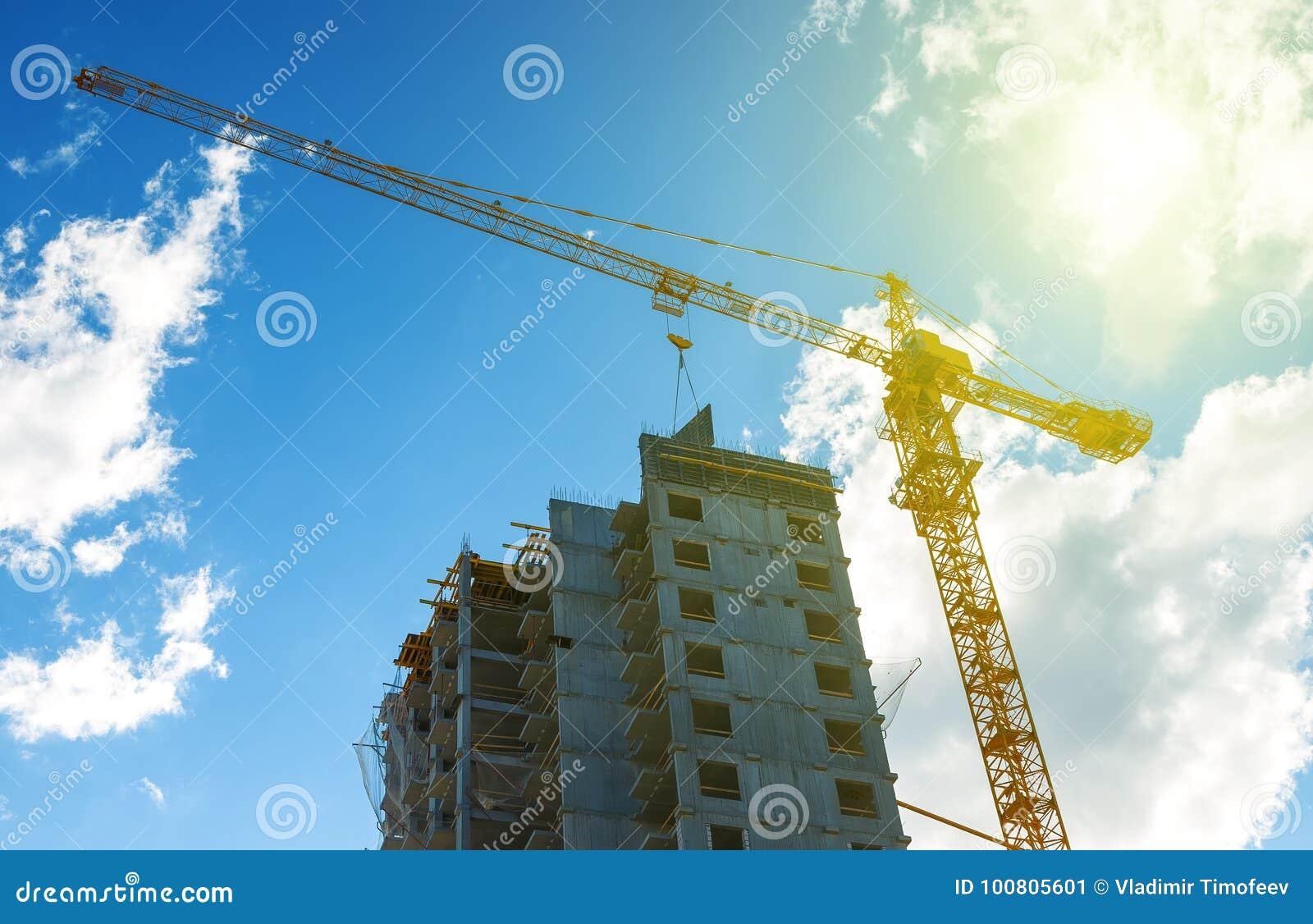 现出轮廓建筑用起重机设备、工业建筑用起重机和大厦在惊人的日落天空摘要