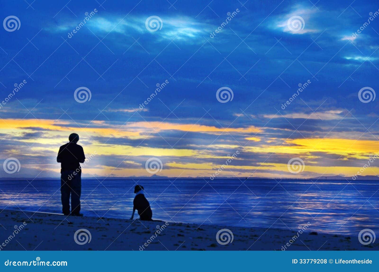 现出轮廓人&他的爱犬单独海洋日落