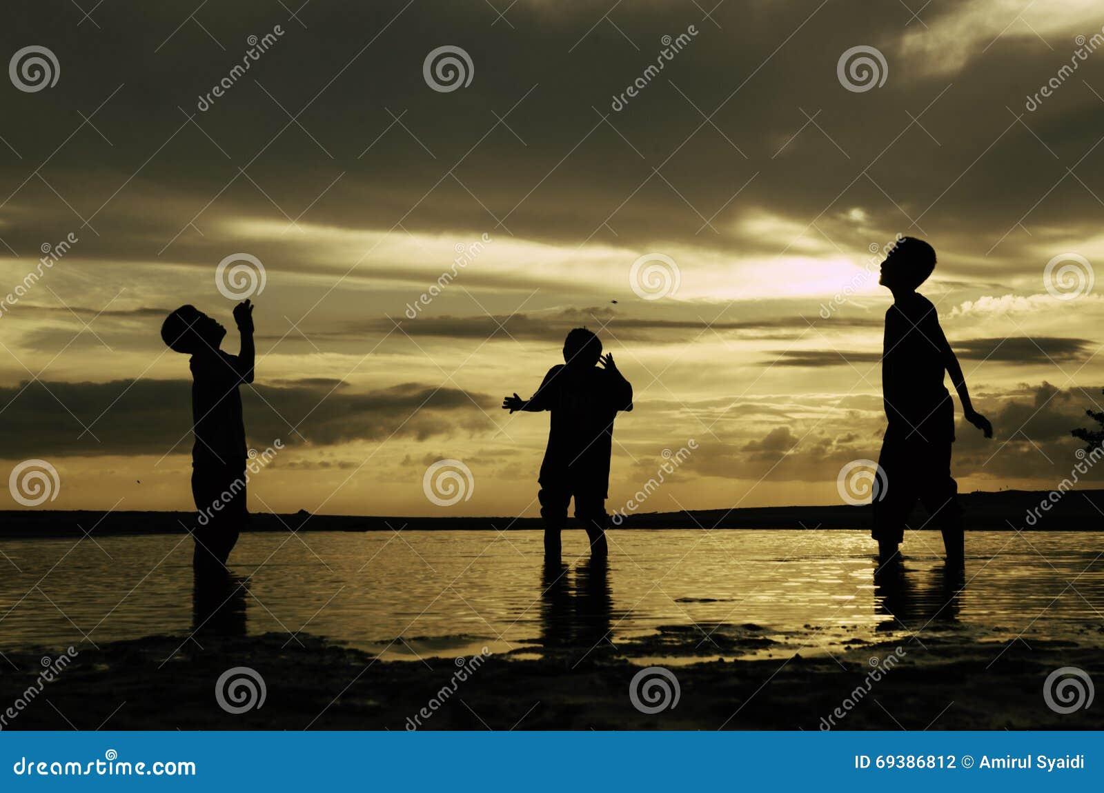 现出轮廓等待愉快的男孩拿到球 与剧烈的云彩的美好的日出日落背景