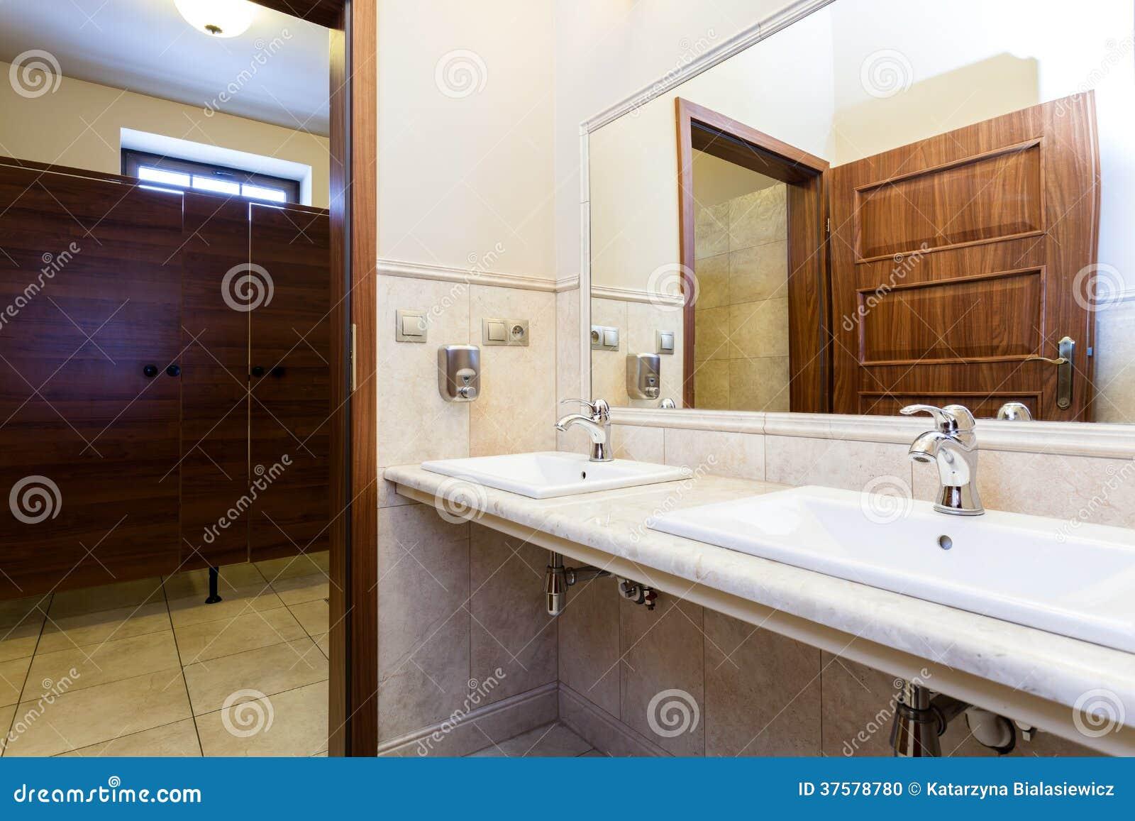 与大理石水槽和木门的现代豪华典雅的时髦的公共厕所.图片