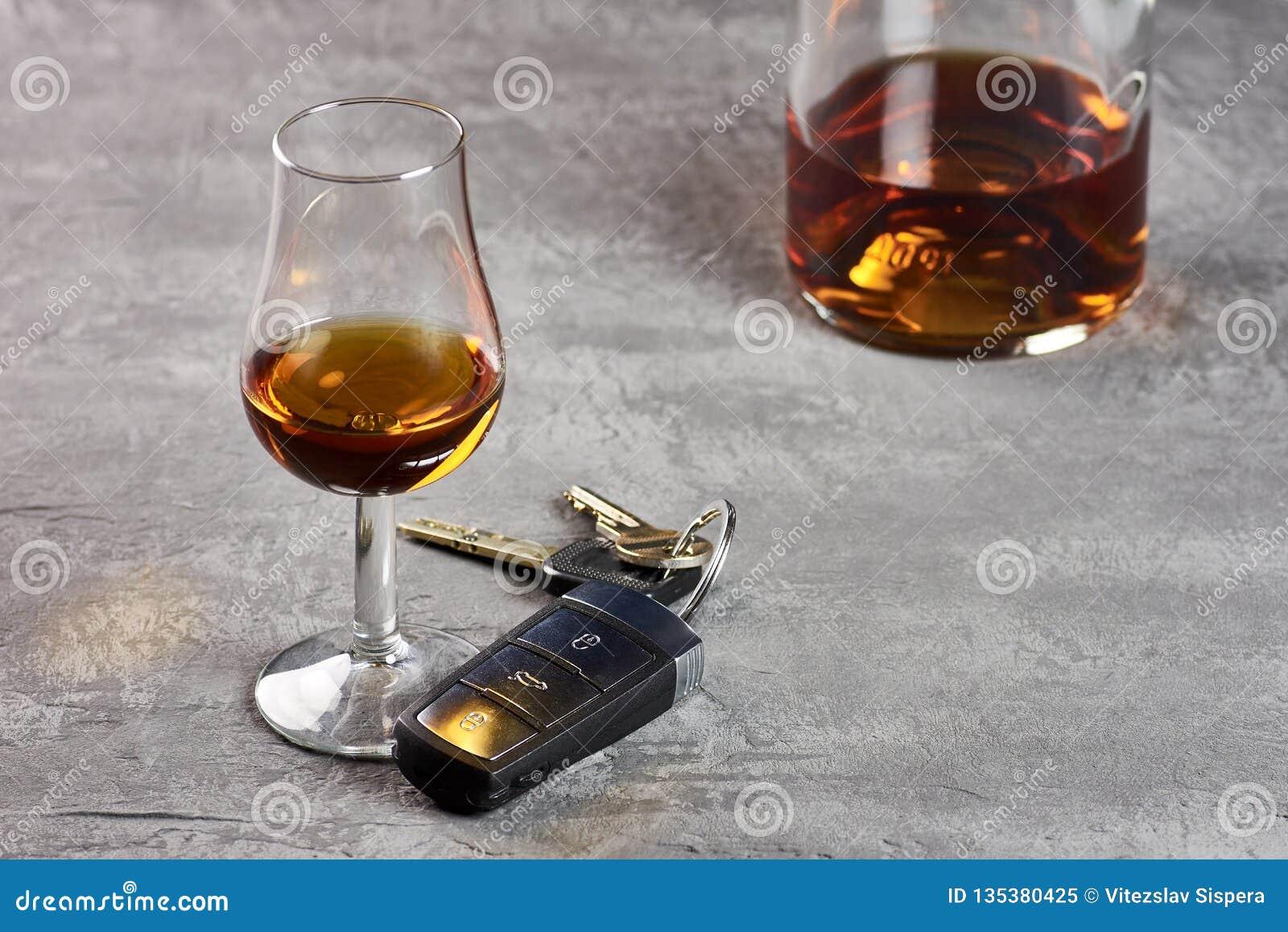 玻璃和瓶在石台式和汽车钥匙的威士忌酒 驾驶在醉态