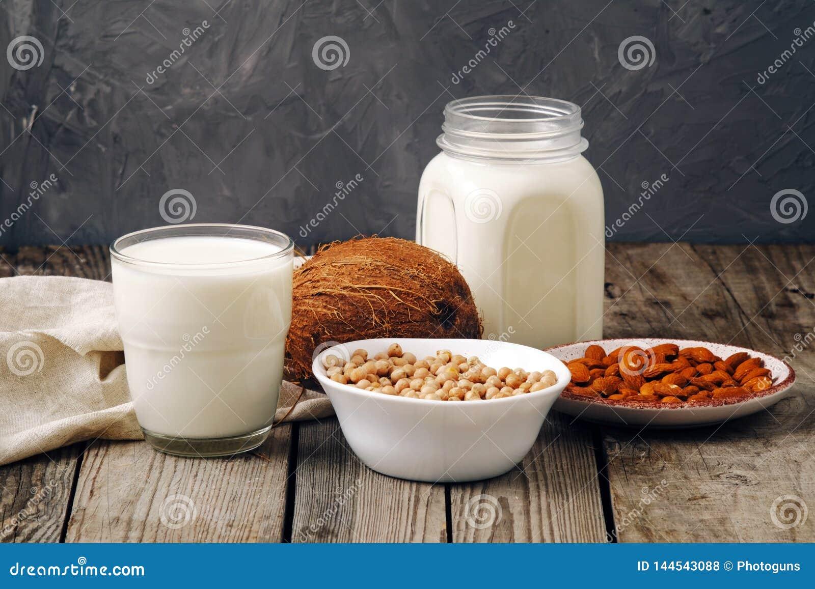 玻璃杯子和瓶子素食主义者植物牛奶和杏仁,坚果,椰子,在木桌上的大豆牛奶 牛奶店自由牛奶替代品饮料和