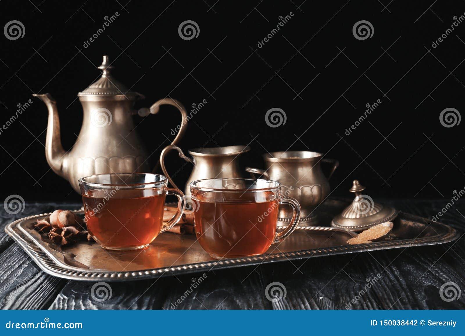 玻璃杯子用在盘子的热的茶反对黑暗的背景