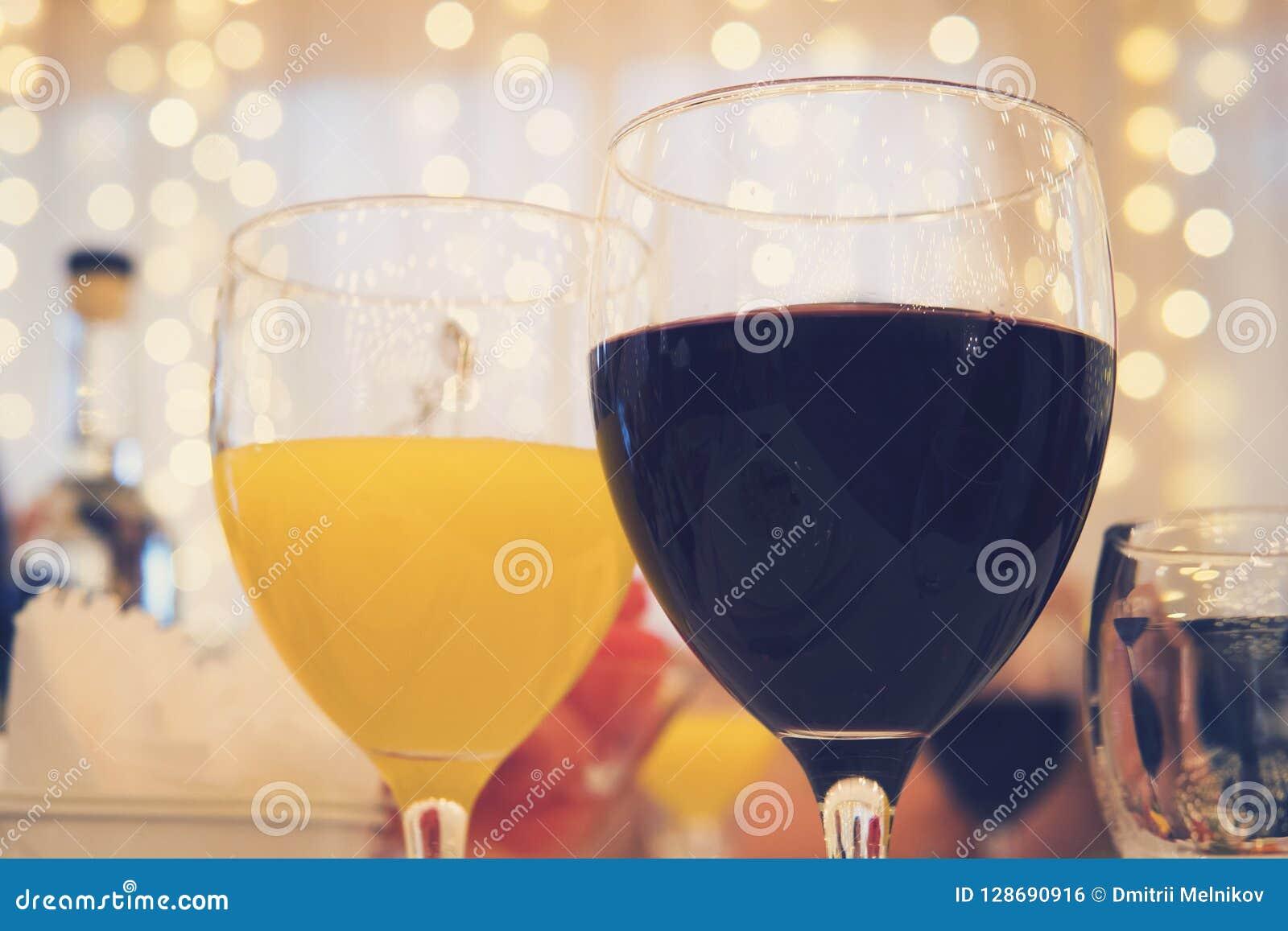 玻璃特写镜头视图用红葡萄酒和橙汁在一张桌上在餐馆诗歌选帷幕背景的 被填装的glasse