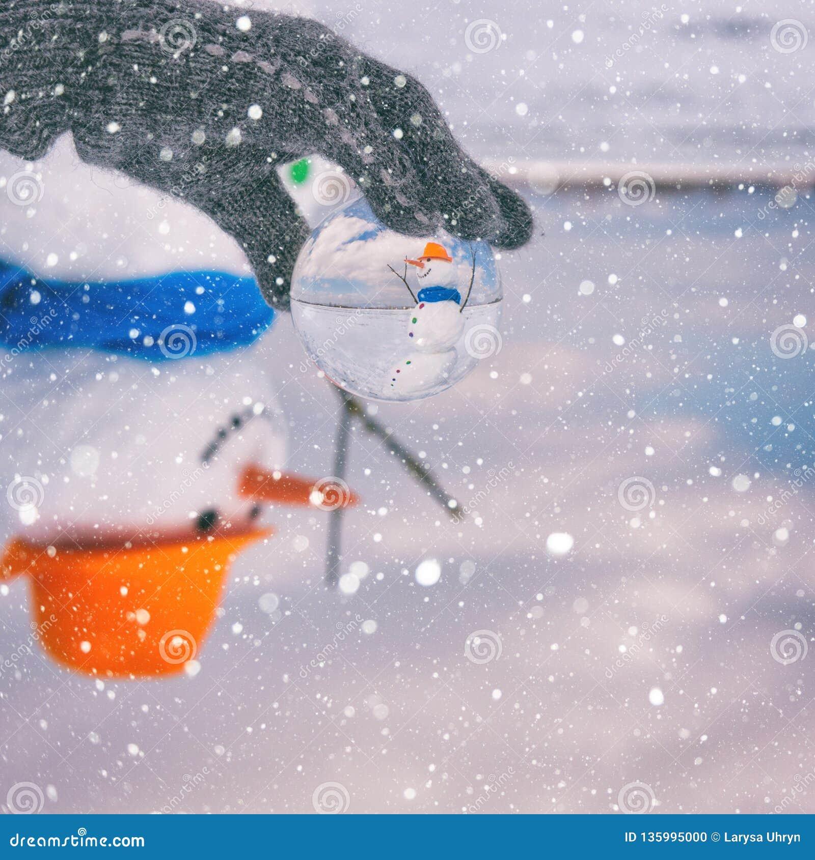 玻璃球的,愉快的冬天,与雪花的五颜六色的背景逗人喜爱的微笑的雪人