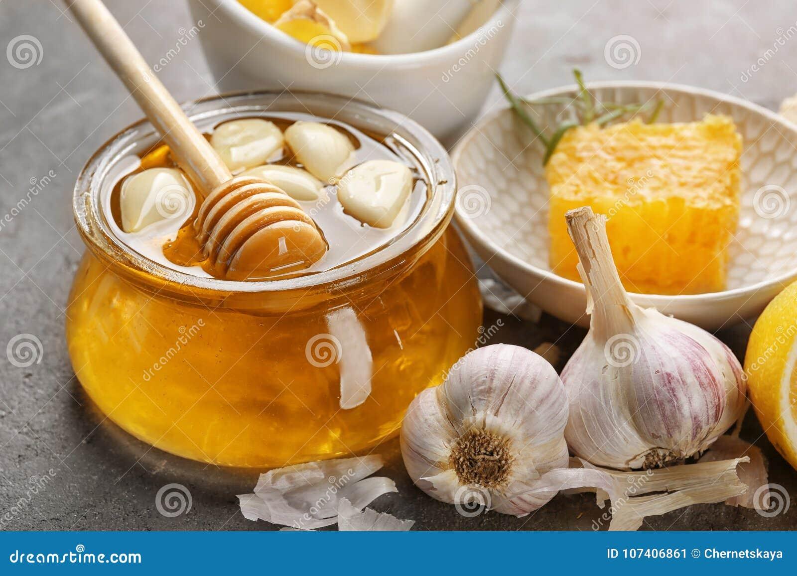 玻璃瓶子用蜂蜜和大蒜在桌上,