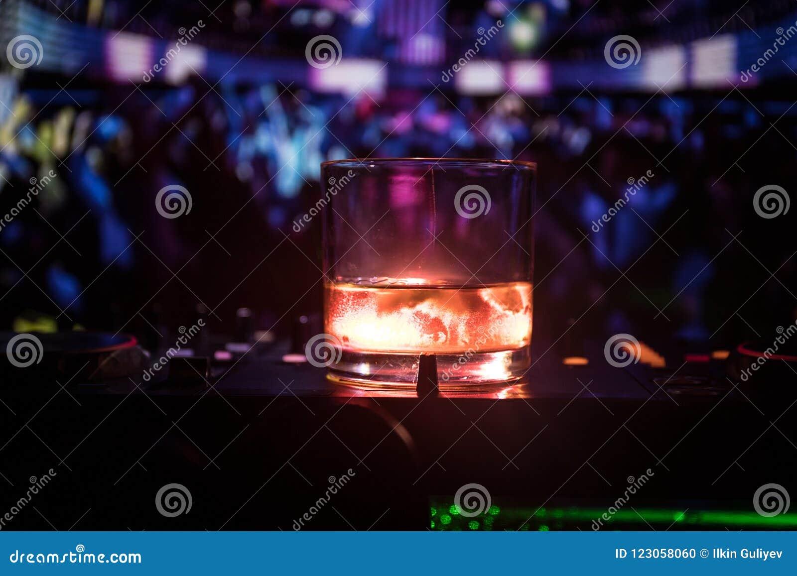 玻璃用与冰块的威士忌酒里面在夜总会的dj控制器 有俱乐部饮料的Dj控制台在音乐党在夜总会与
