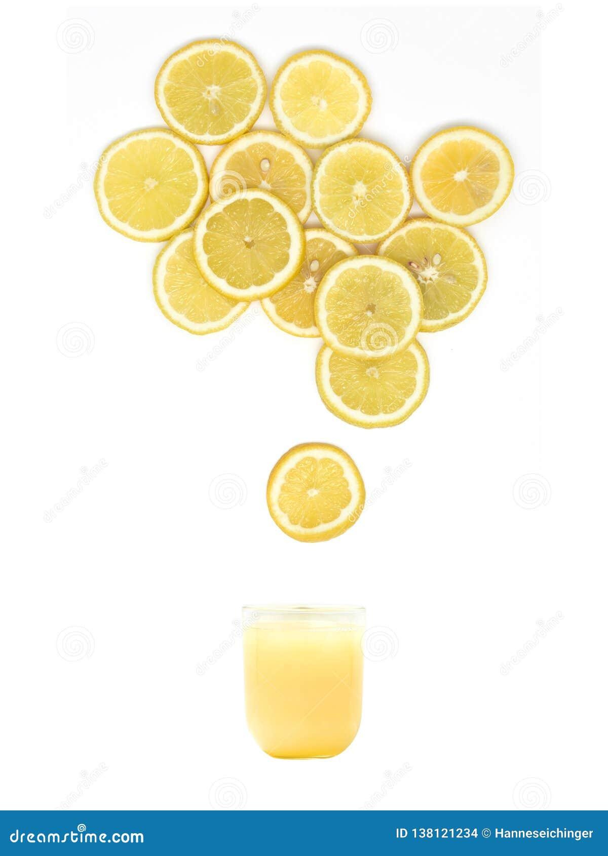 玻璃用新鲜的柠檬汁站立在白色背景的许多柠檬切片下