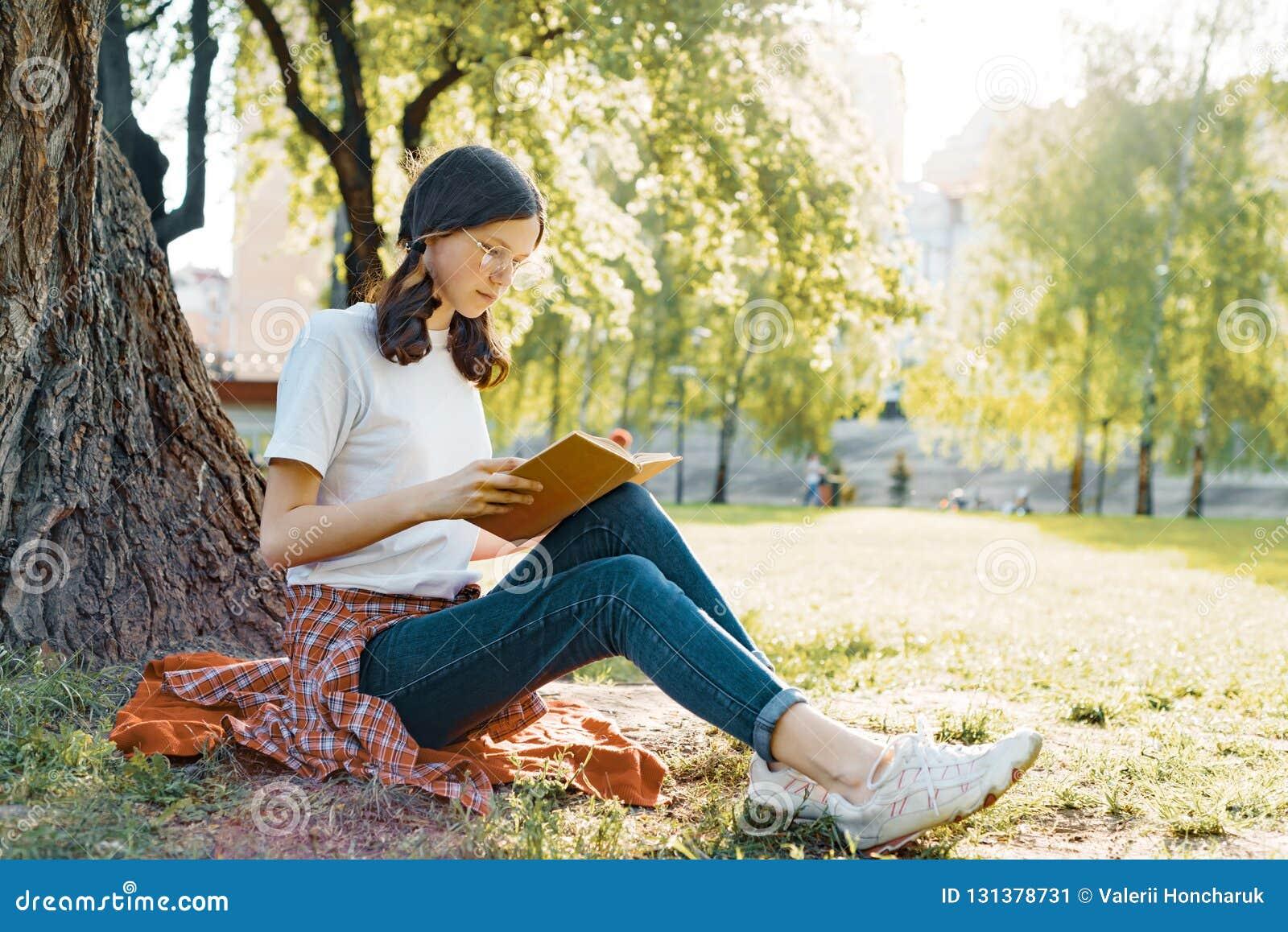 玻璃的女生读一本书的在坐在树下的公园在草