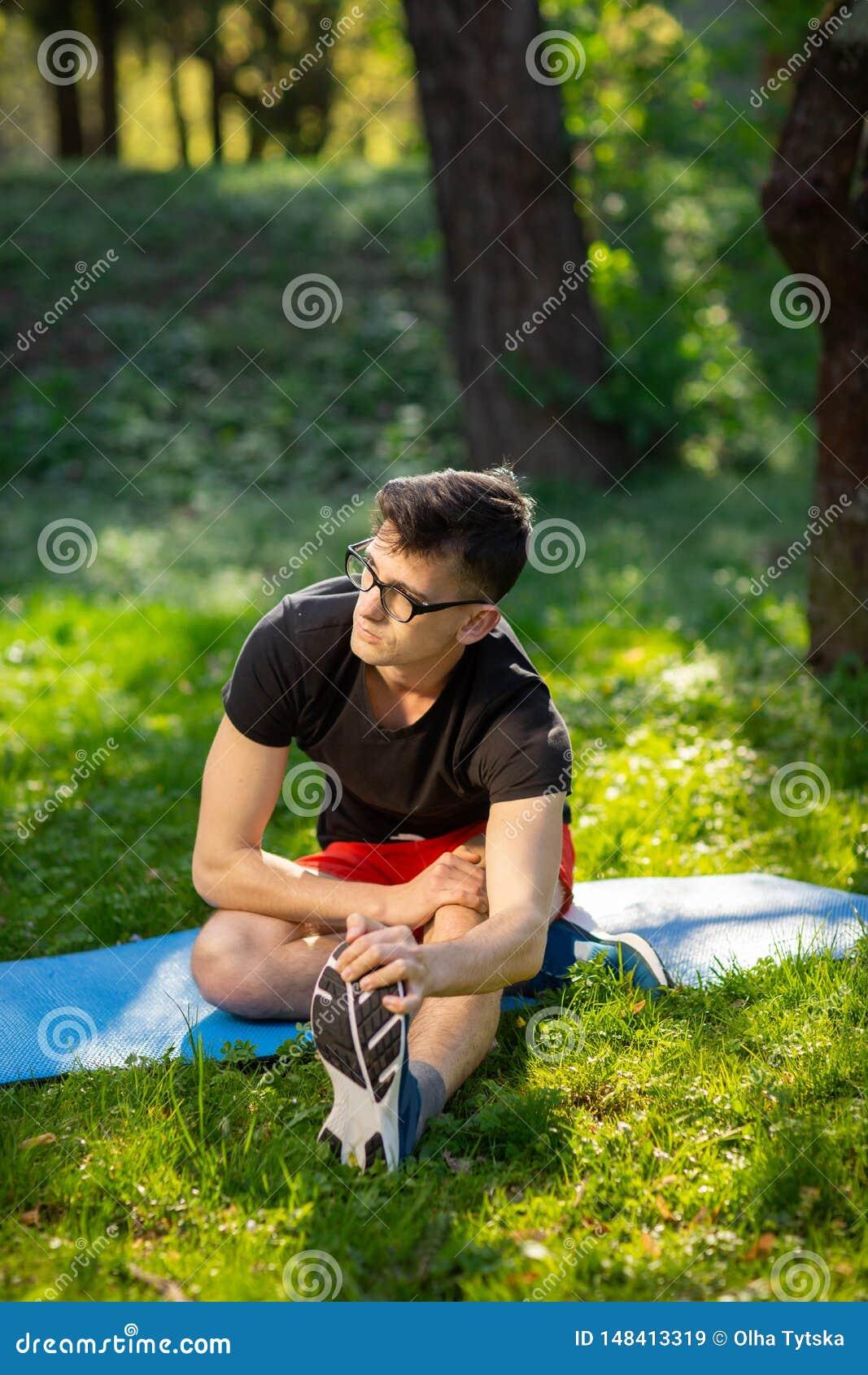 玻璃的年轻人训练瑜伽的户外 运动的人在一张蓝色瑜伽席子做放松的锻炼,在公园 r