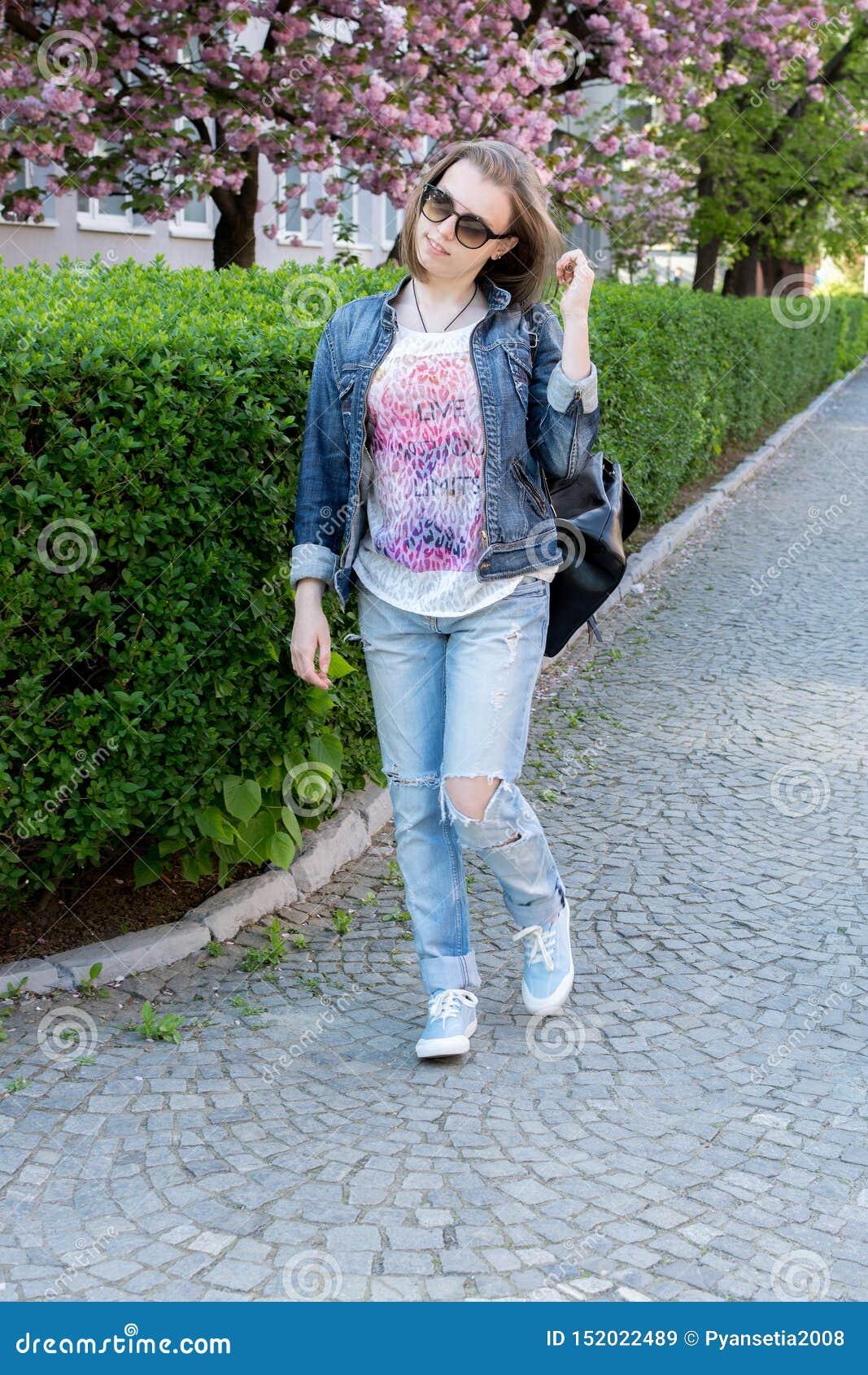 玻璃的青少年的女孩走在一个开花的佐仓公园的 步行在早期的春天