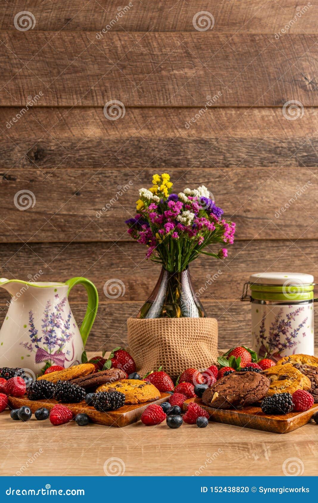 玻璃花瓶用狂放的莓果和巧克力饼干在木板