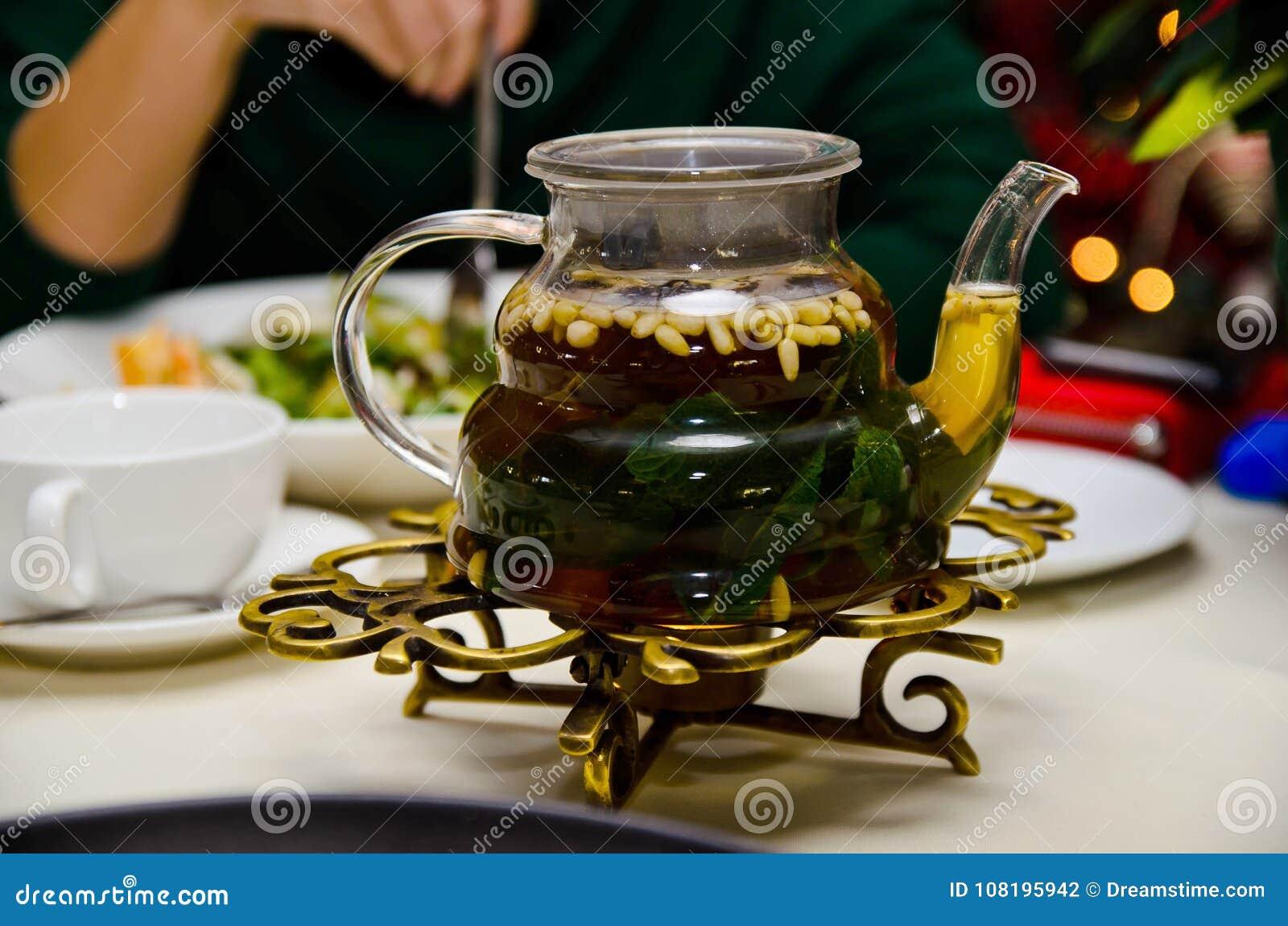 玻璃teaspot用薄荷的茶和在桌上的松子
