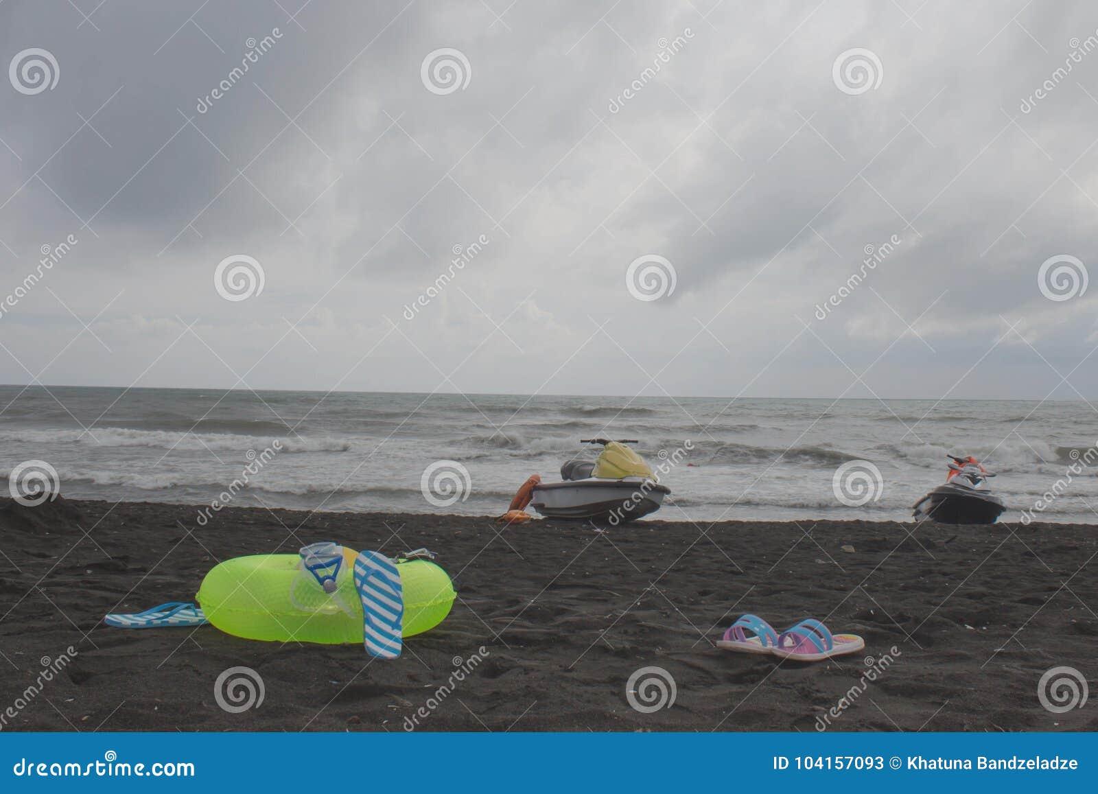 球、游泳的玻璃、凉鞋、水滑行车和浮动圆环在海滩 阴云密布,浪涌
