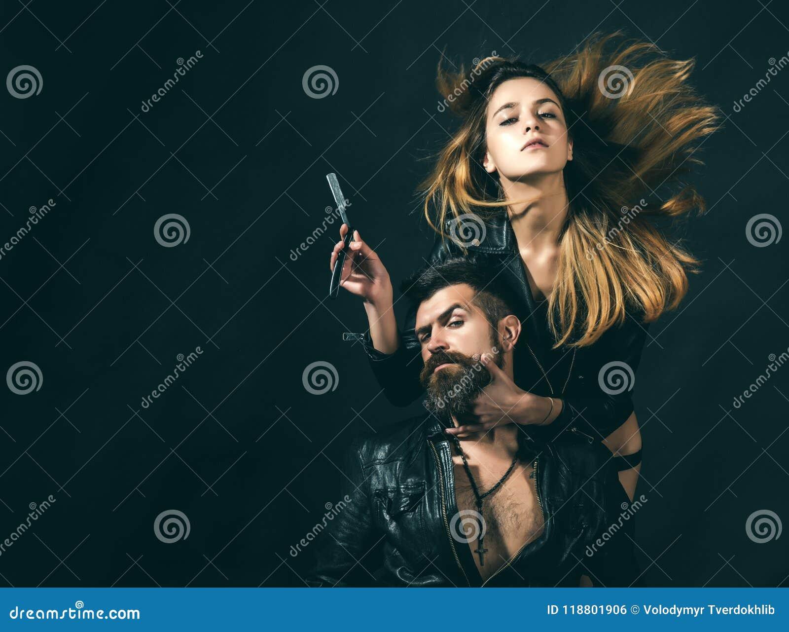 理发师概念 性感的女孩和残酷有胡子的行家夫妇有髭的,黑背景 有直接的理发师