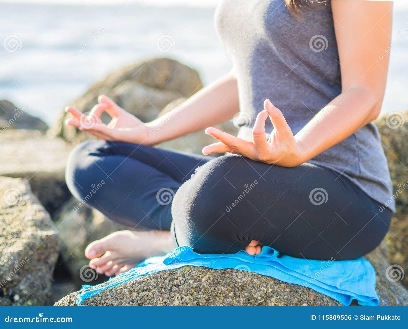 瑜伽概念 在海滩的特写镜头妇女手实践的莲花姿势在日落