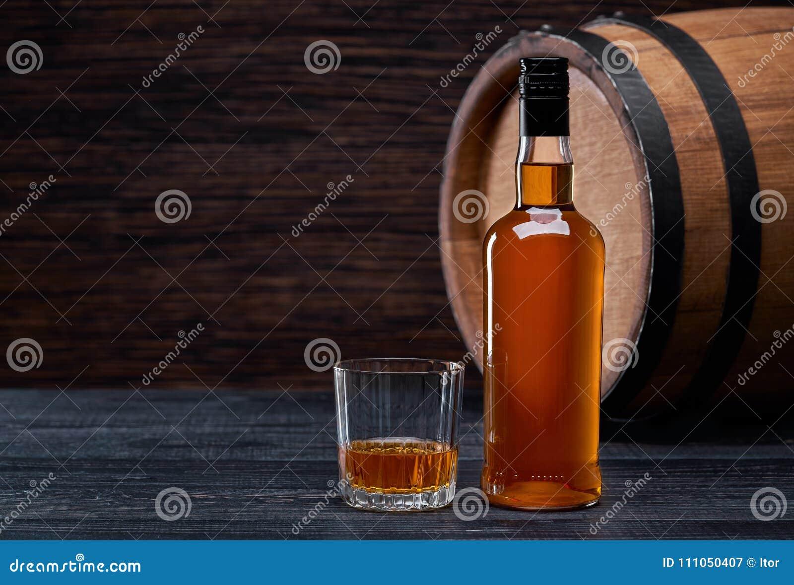瓶在黑色的威士忌酒木在橡木滚磨